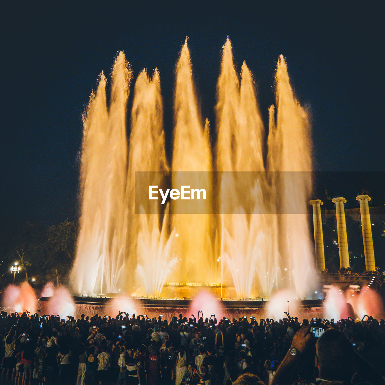 Crowd watching huge fountain against sky at night