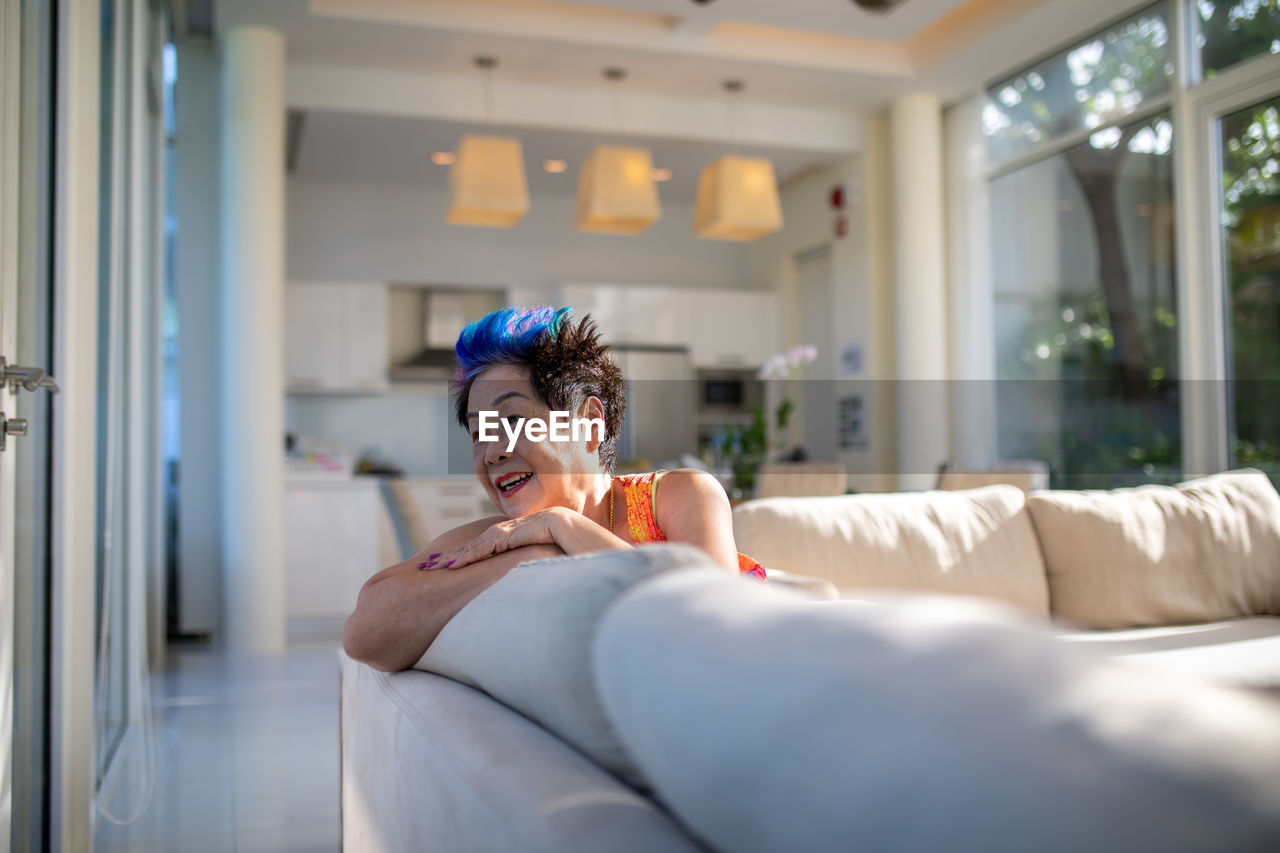 Smiling Woman With Dyed Hair Sitting On Sofa At Home