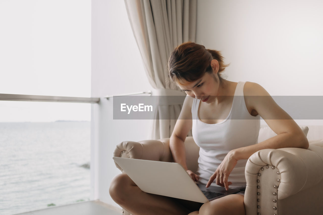 YOUNG WOMAN LOOKING AT CAMERA WHILE SITTING ON LAPTOP