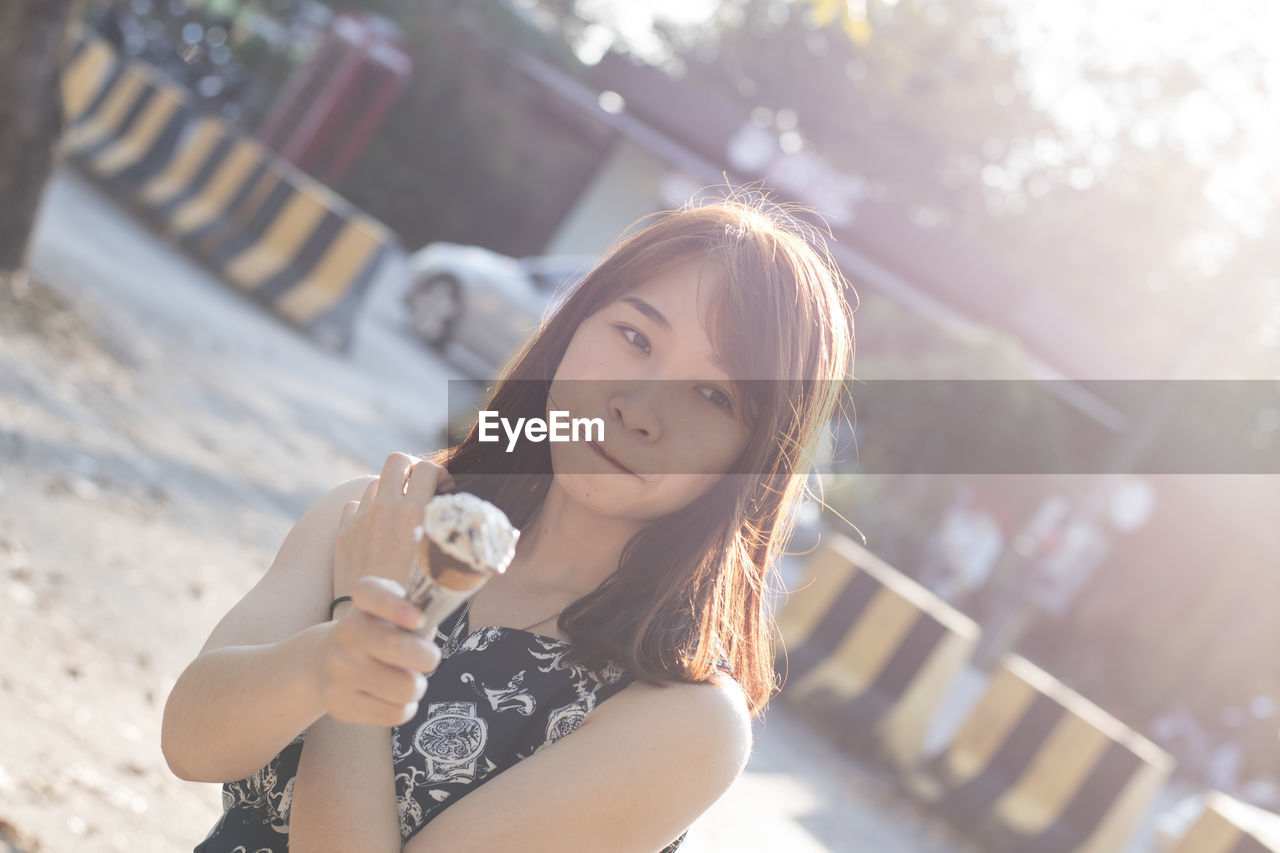 Portrait of young woman eating ice cream while standing in city