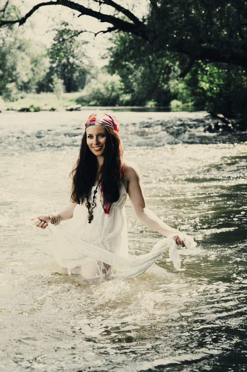 Portrait Of Young Woman Standing In River Against Trees
