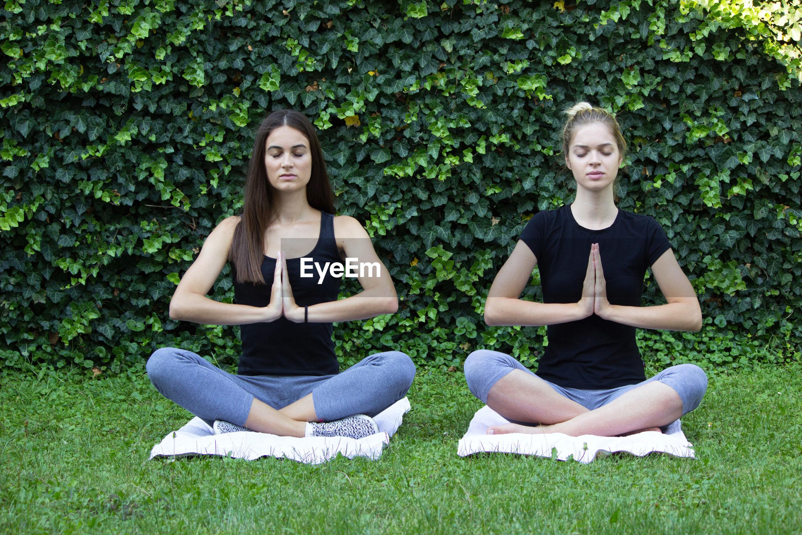 Beautiful young women doing yoga in park