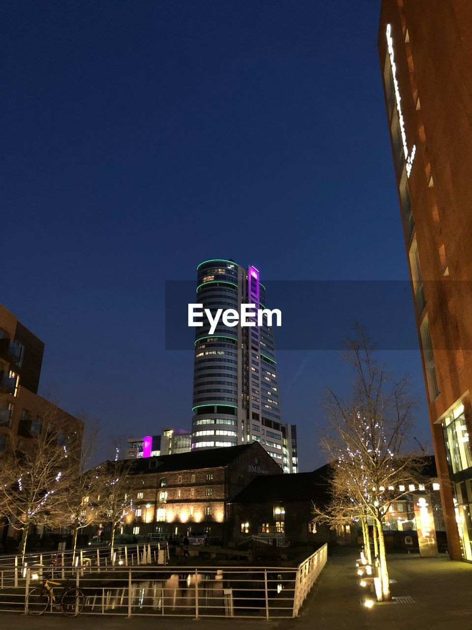building exterior, architecture, sky, illuminated, built structure, city, night, building, low angle view, nature, clear sky, tree, office building exterior, no people, skyscraper, plant, lighting equipment, blue, office, tall - high, outdoors, modern