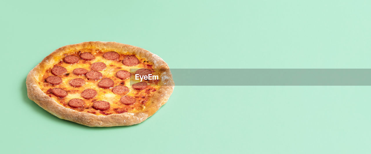 HIGH ANGLE VIEW OF PIZZA AGAINST BLACK BACKGROUND