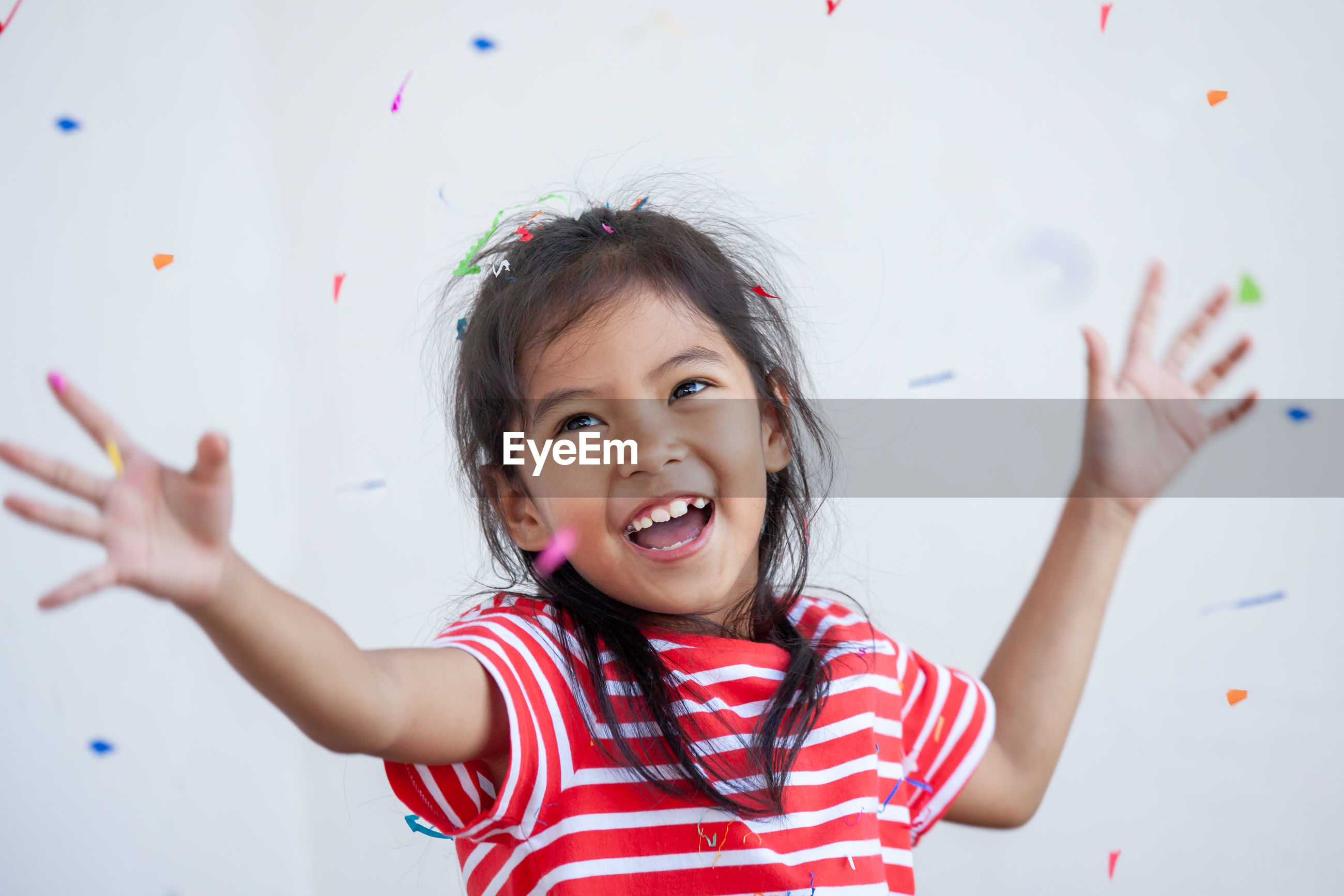 Cheerful girl with confetti against white background