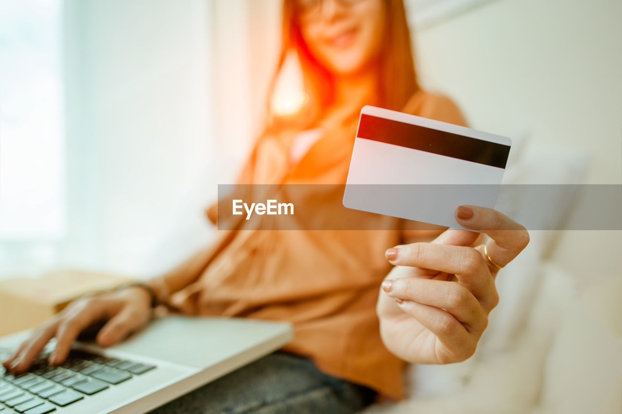 Midsection of woman holding credit card at home