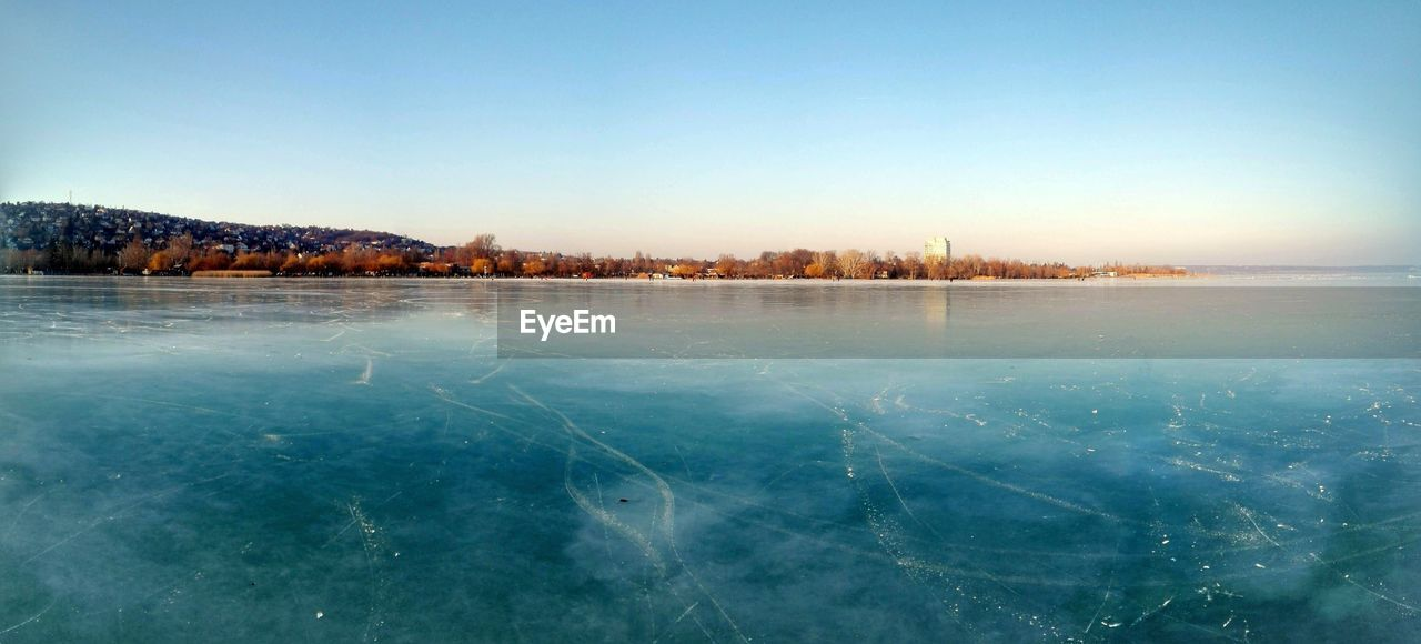 tranquility, beauty in nature, tranquil scene, scenics, cold temperature, winter, nature, lake, no people, outdoors, frozen, water, landscape, clear sky, snow, sky, blue, day, tree