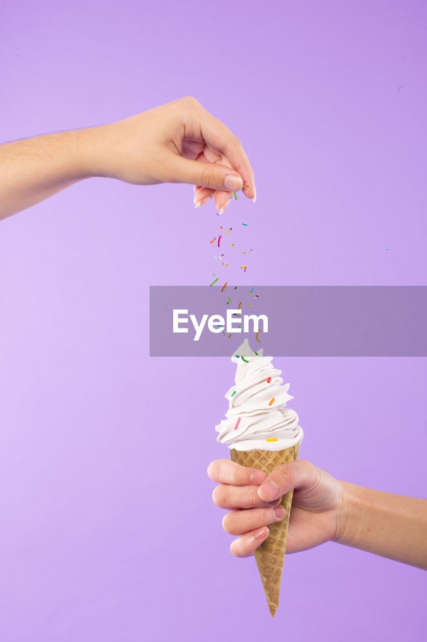 Cropped Hands Sprinkling Sprinkles On Ice Cream | on EyeEm