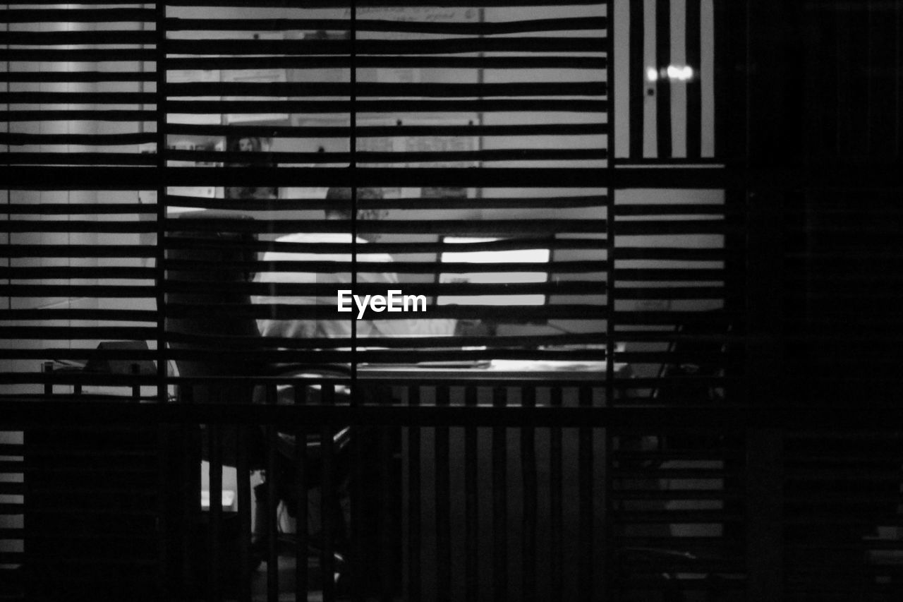 Man working in office seen through blinds
