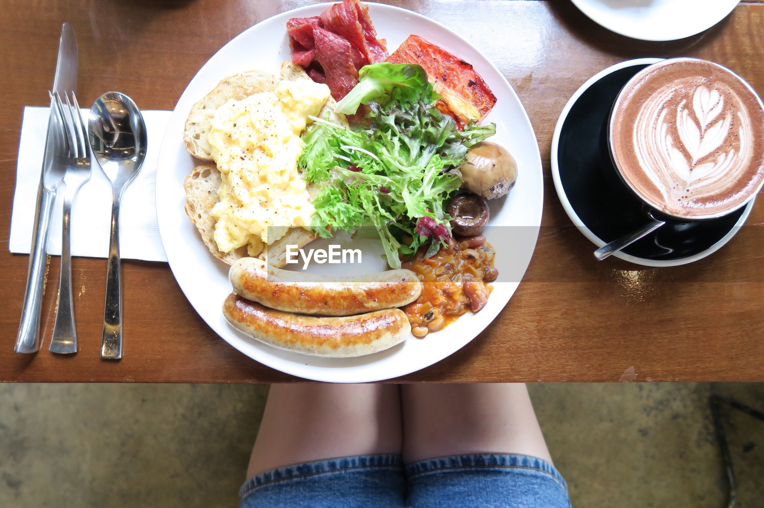 Low section of person with breakfast on table