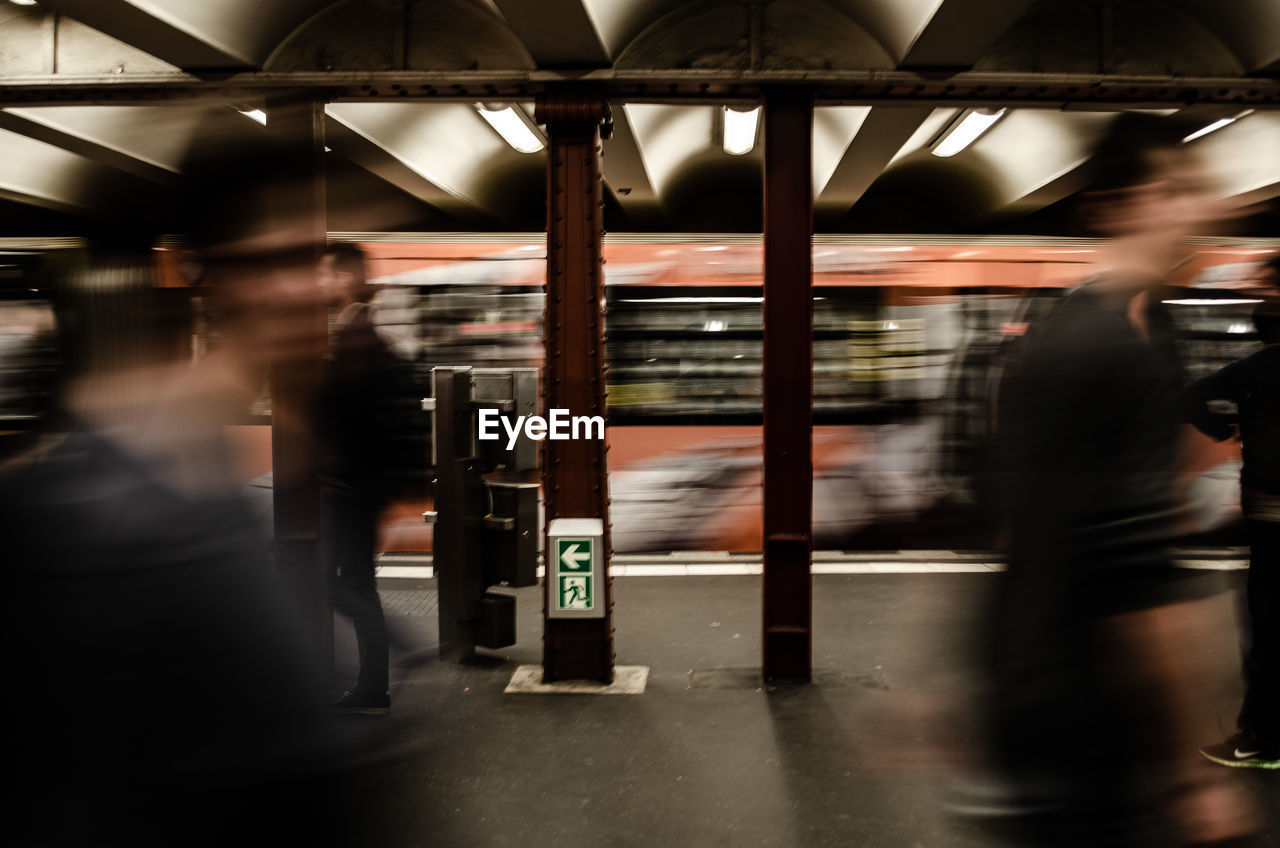 Blurred motion of people walking by train at subway station