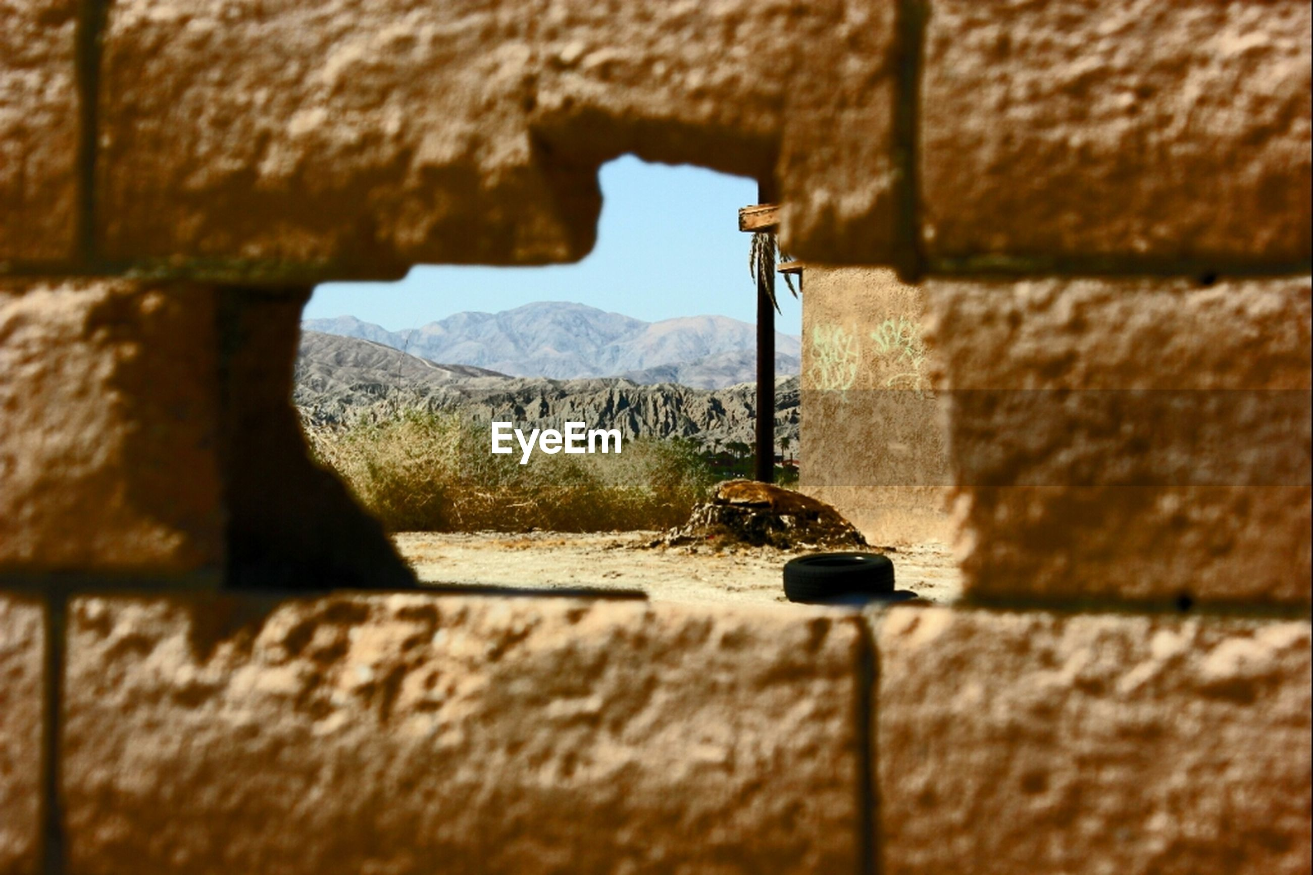 built structure, selective focus, architecture, wall - building feature, wall, building exterior, focus on foreground, close-up, stone wall, brick wall, surface level, metal, day, old, outdoors, no people, focus on background, house, sunlight, sky