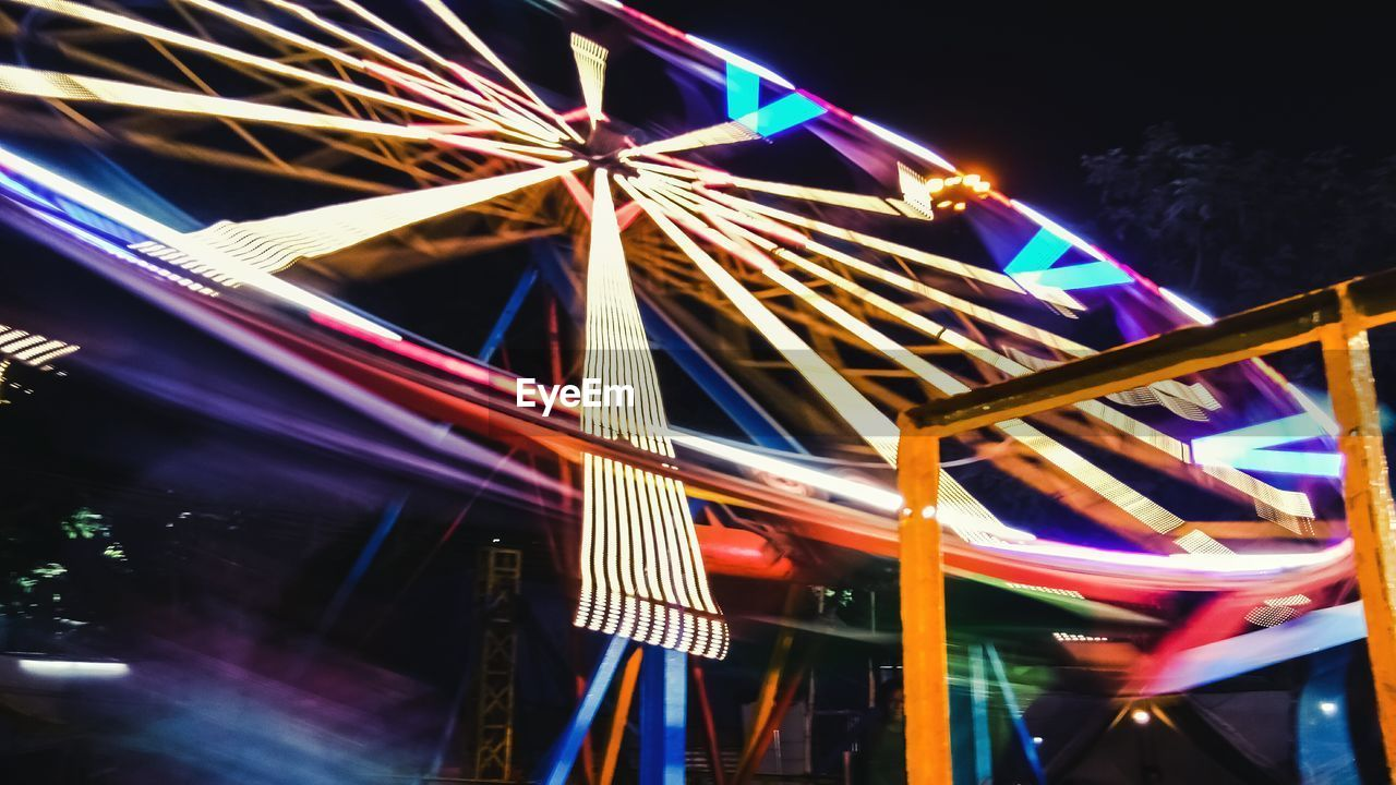 illuminated, night, multi colored, long exposure, architecture, glowing, blurred motion, motion, no people, built structure, arts culture and entertainment, amusement park, light - natural phenomenon, light trail, building exterior, amusement park ride, speed, lighting equipment, low angle view, celebration