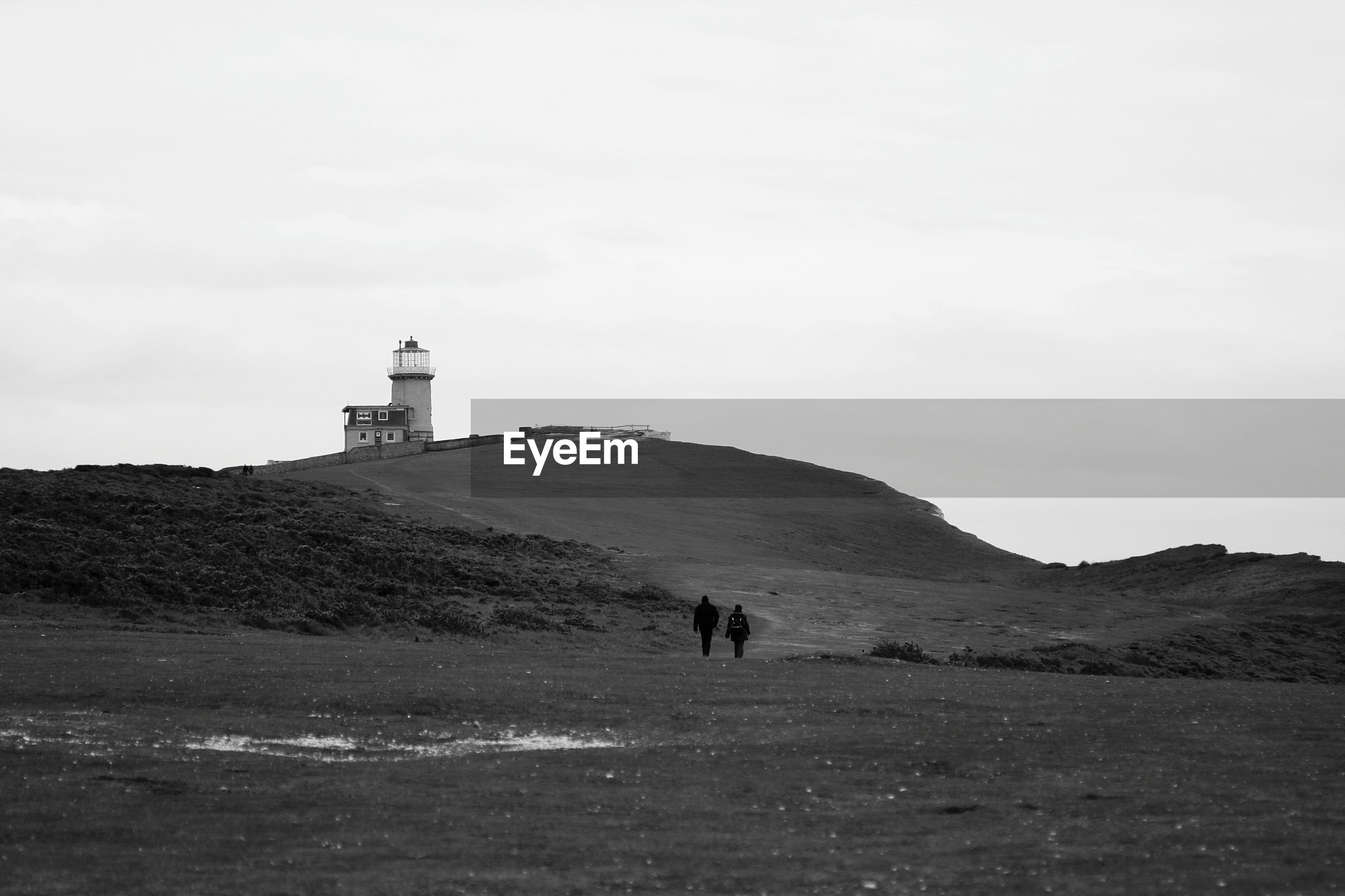 People on lighthouse at seaside