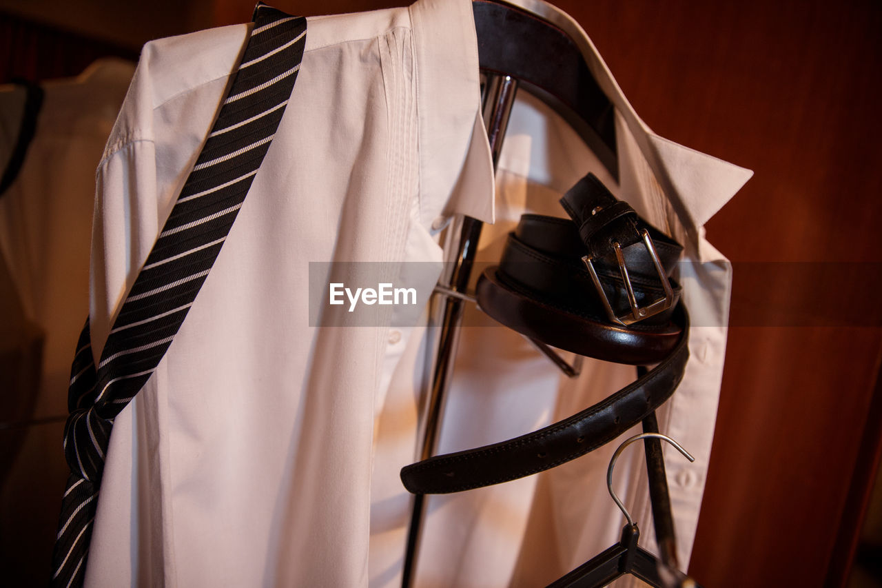 Close-up of necktie and shirt with belt on coathanger