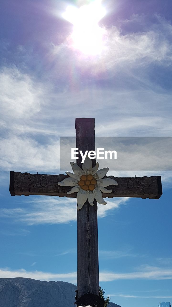 sky, nature, cloud - sky, low angle view, cross, sunlight, flower, day, no people, flowering plant, religion, sunbeam, spirituality, belief, plant, wood - material, beauty in nature, sun, communication