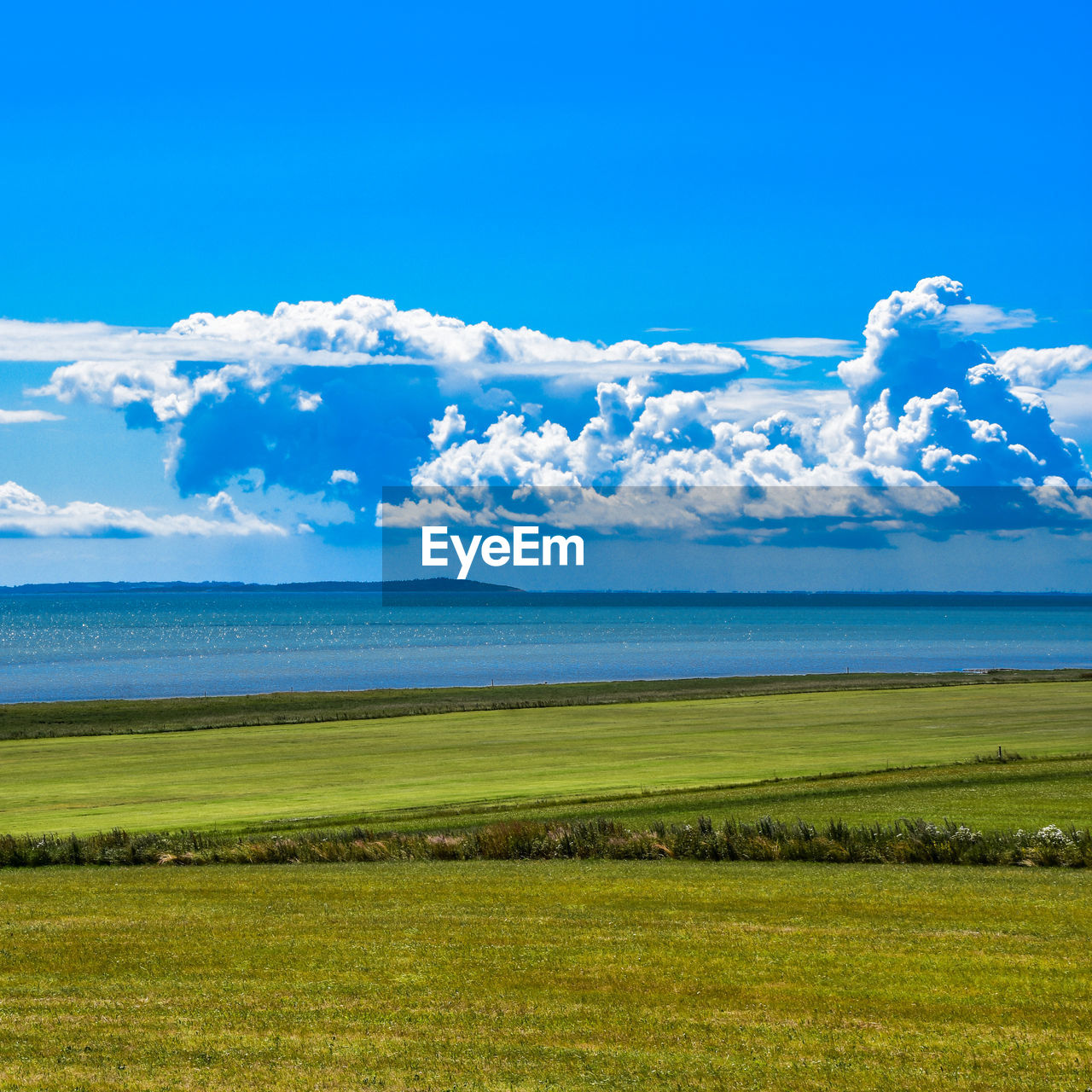sky, scenics - nature, tranquil scene, beauty in nature, tranquility, cloud - sky, grass, water, plant, land, blue, day, environment, horizon, no people, landscape, nature, green color, non-urban scene, horizon over water, outdoors
