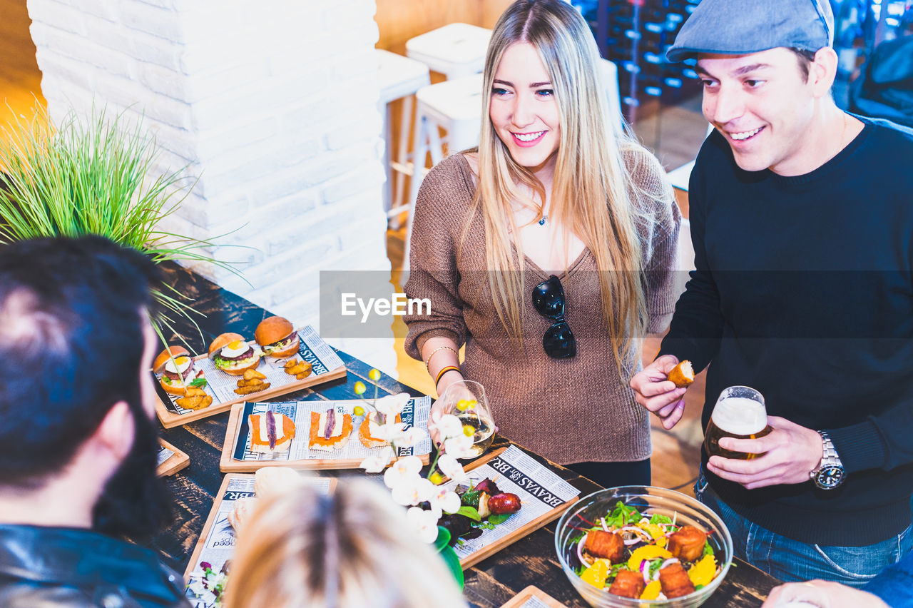 High Angle View Of Happy Friends Having Food At Table In Bar
