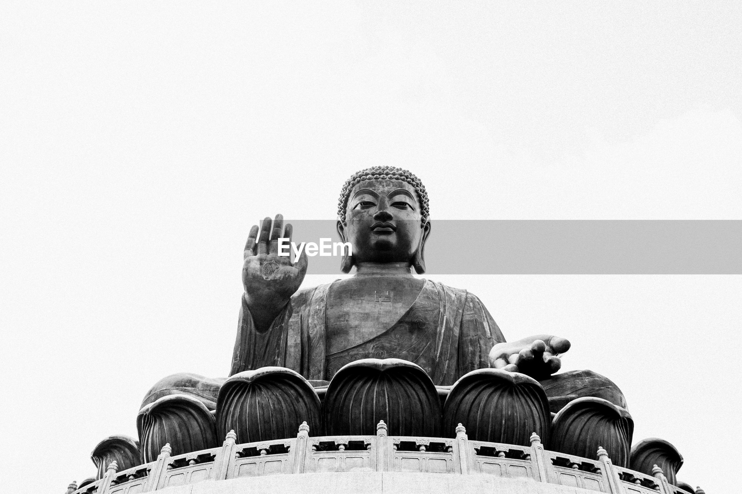 Low angle view of statue against temple against clear sky