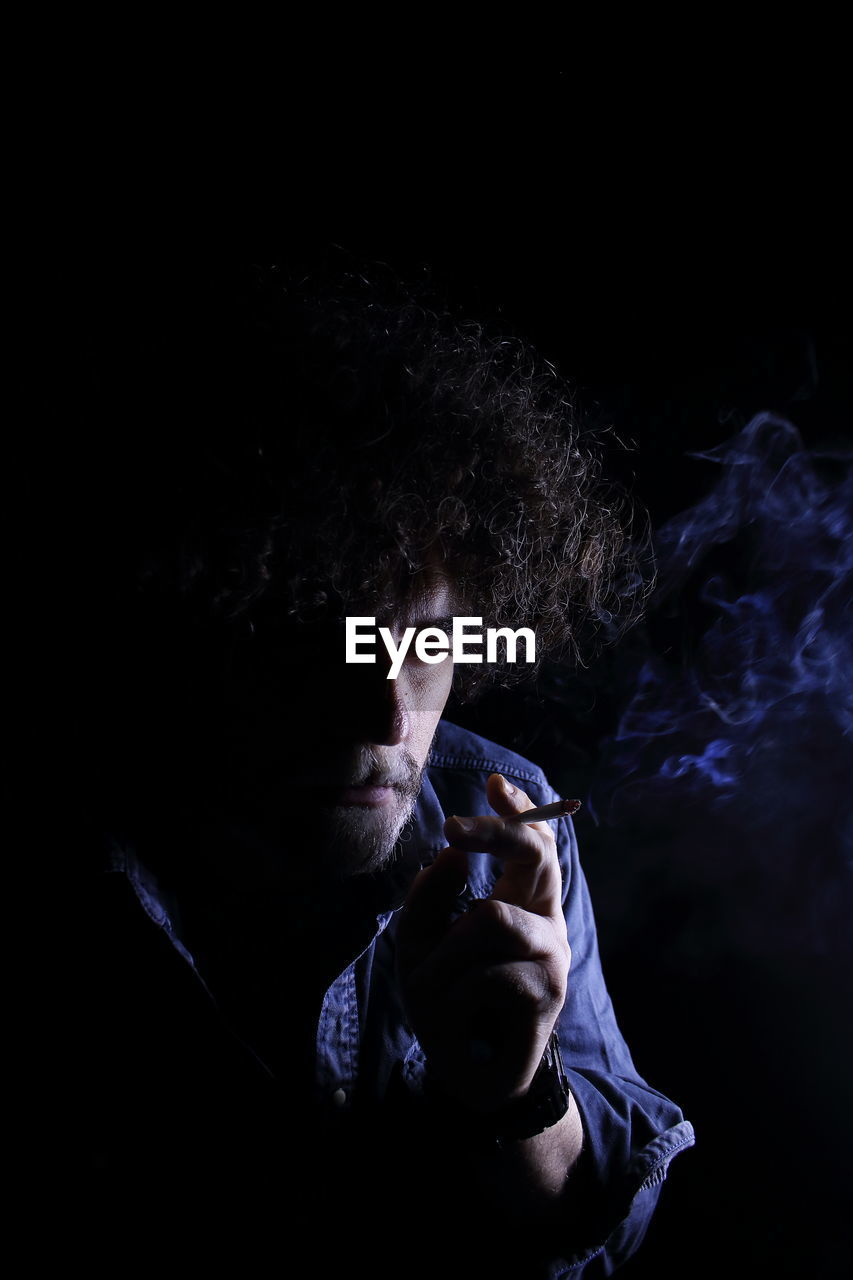 Man Smoking Against Black Background
