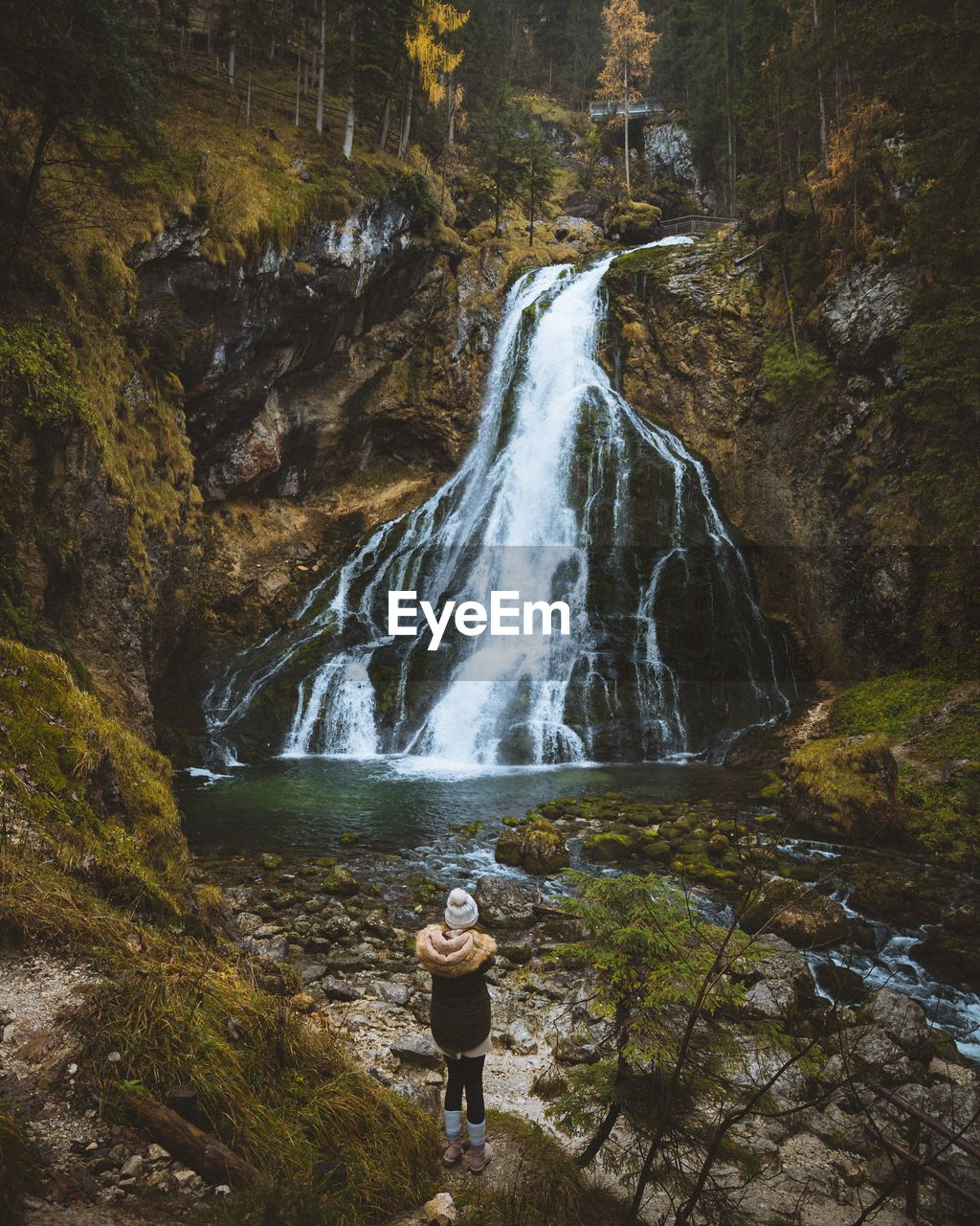 Rear View Of Woman Standing Near Waterfall