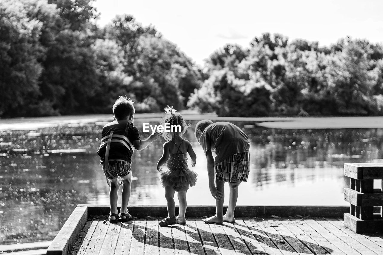 Rear view of children standing by lake