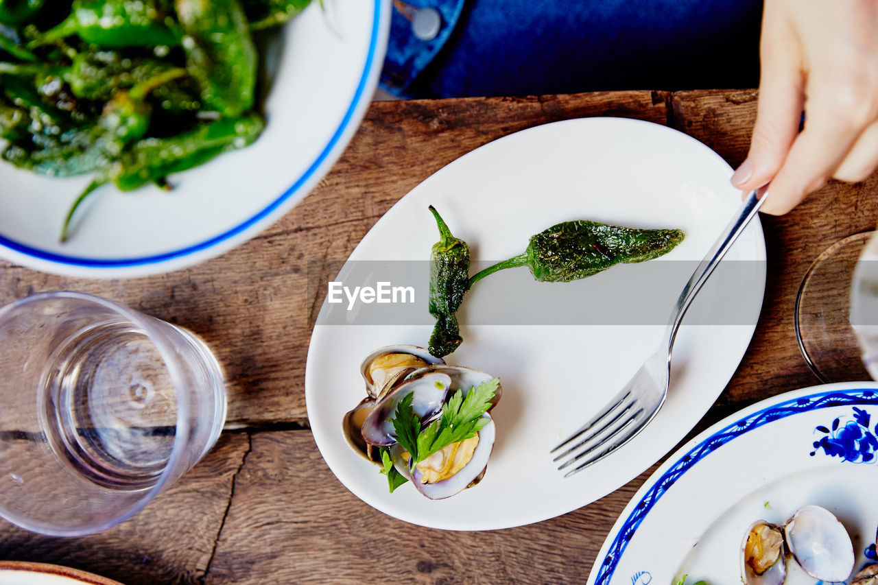 food and drink, freshness, table, indoors, food, plate, high angle view, vegetable, healthy eating, human hand, cutting board, ready-to-eat, refreshment, one person, drink, close-up, human body part, real people, day