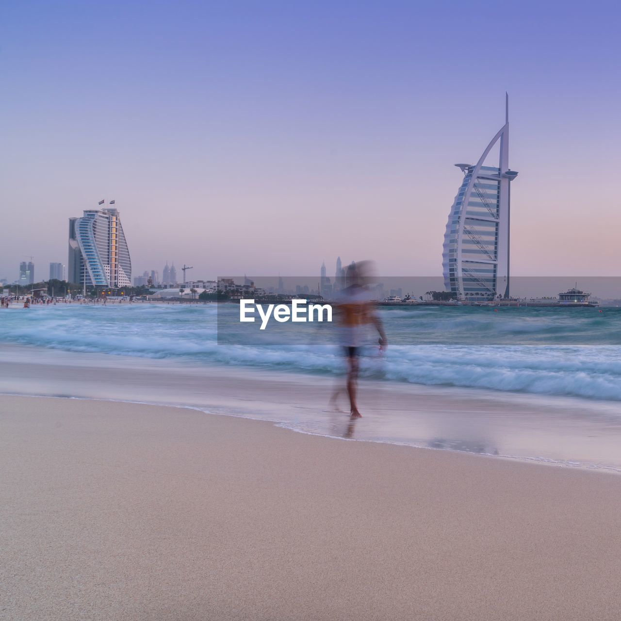 water, sky, sea, motion, architecture, land, city, building exterior, beach, built structure, blurred motion, office building exterior, nature, building, travel destinations, one person, real people, sand, urban skyline, skyscraper, tall - high, cityscape, outdoors