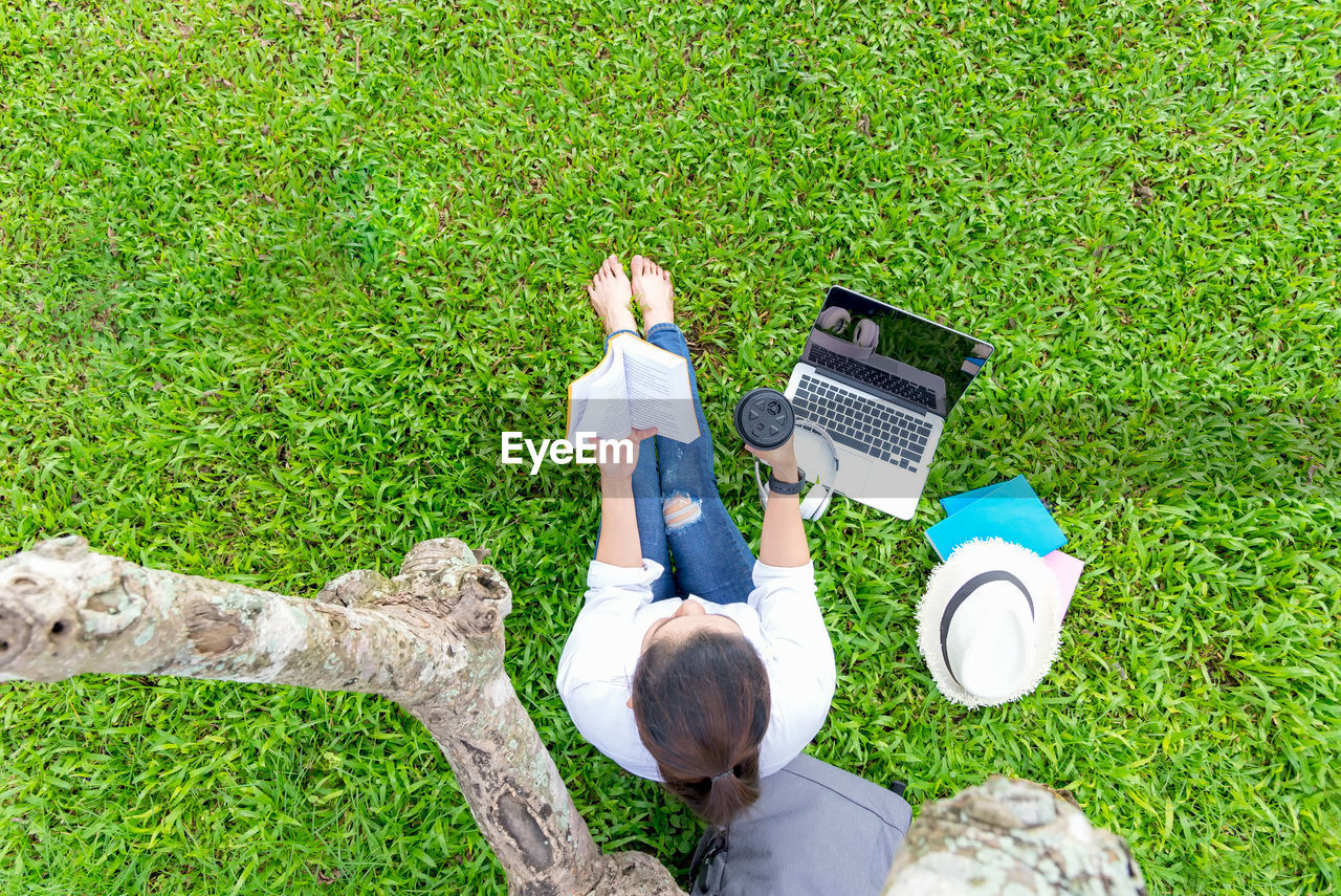 HIGH ANGLE VIEW OF WOMAN STANDING ON GRASS