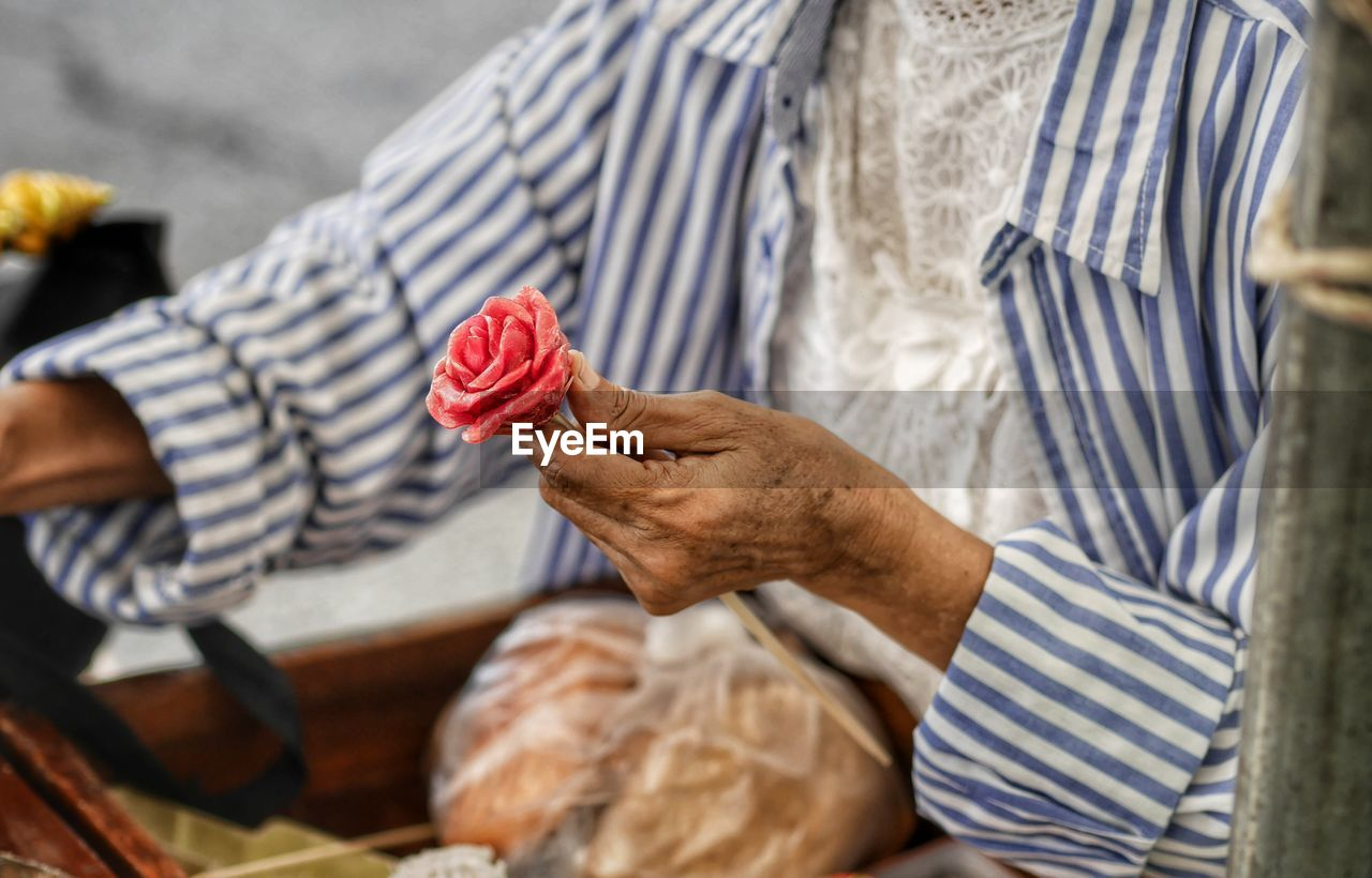hand, human hand, holding, midsection, one person, real people, men, human body part, striped, casual clothing, freshness, focus on foreground, occupation, day, lifestyles, indoors, food, food and drink, clothing, finger