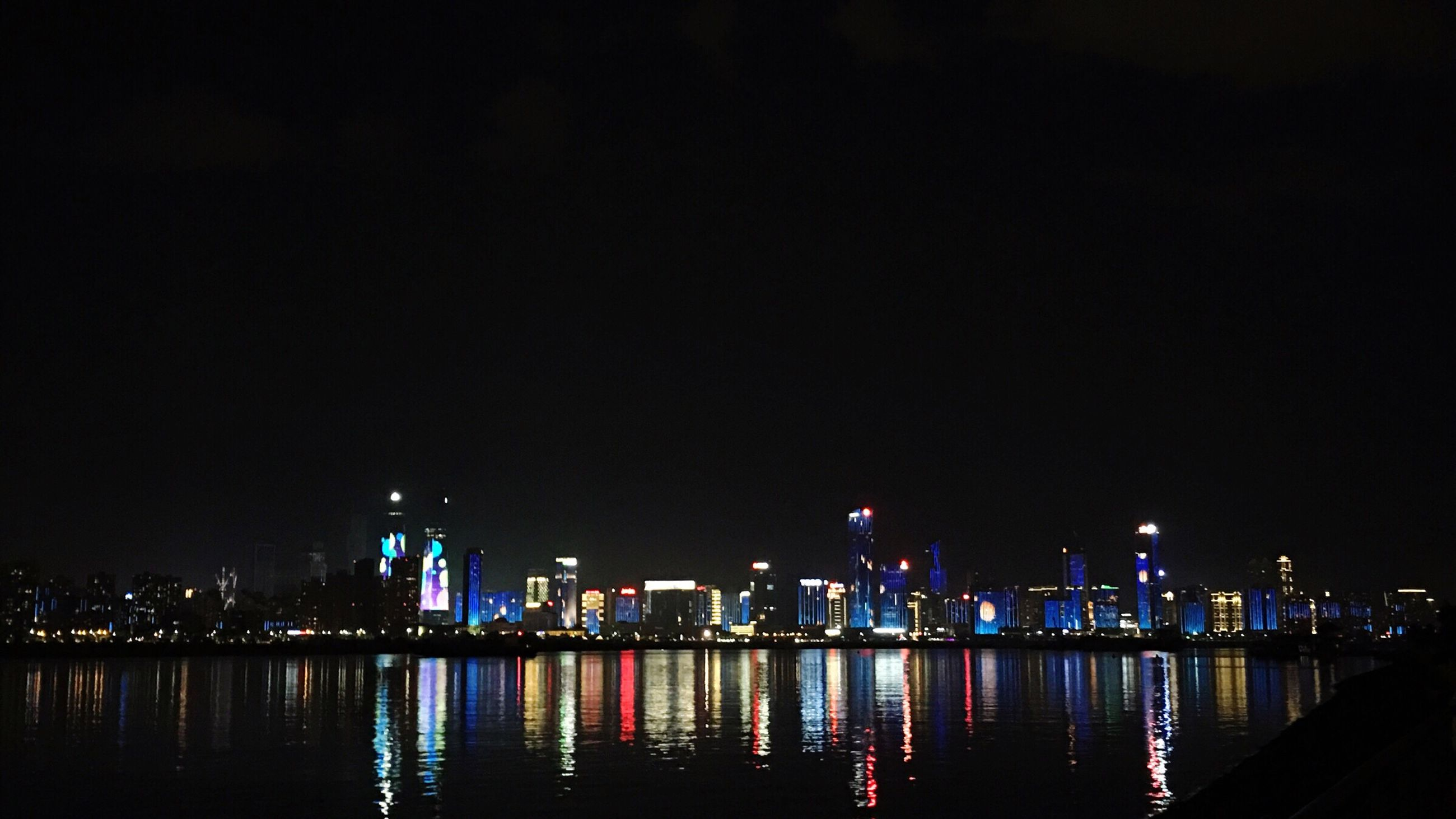 night, illuminated, architecture, building exterior, built structure, city, skyscraper, cityscape, copy space, travel destinations, urban skyline, water, waterfront, reflection, no people, sky, city life, modern, river, outdoors, clear sky, nature