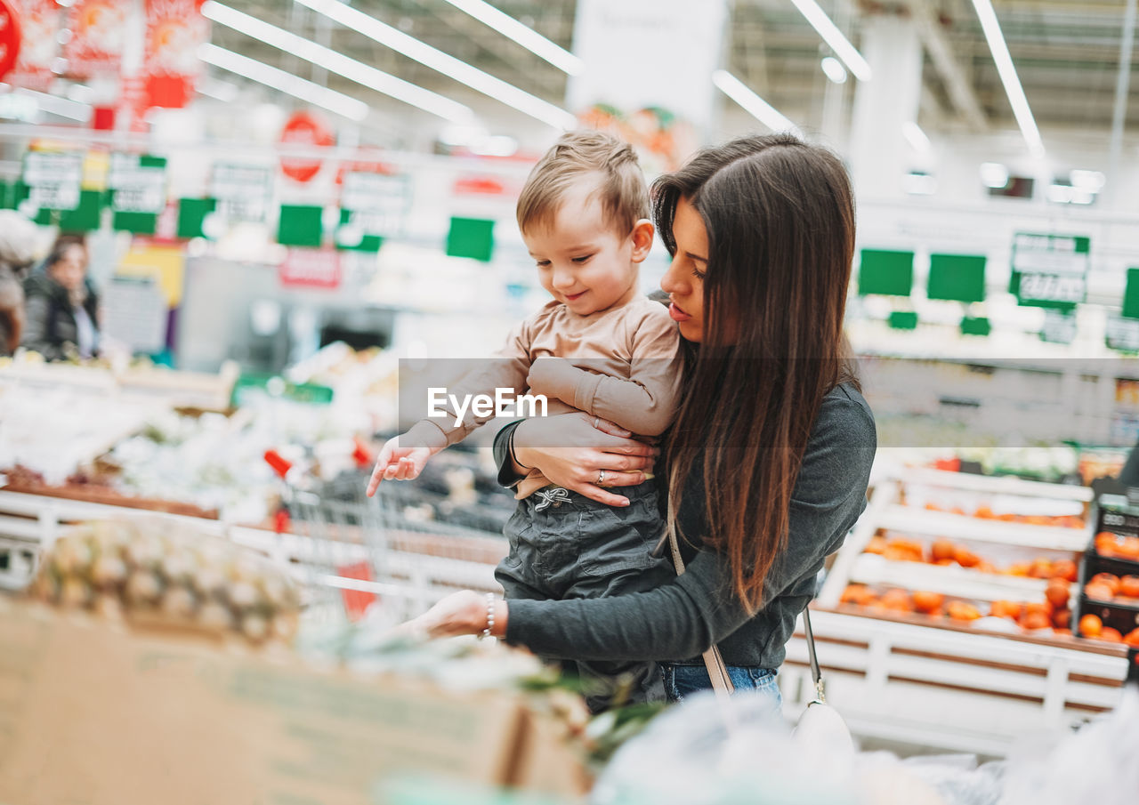 Young woman with baby boy standing in supermarket