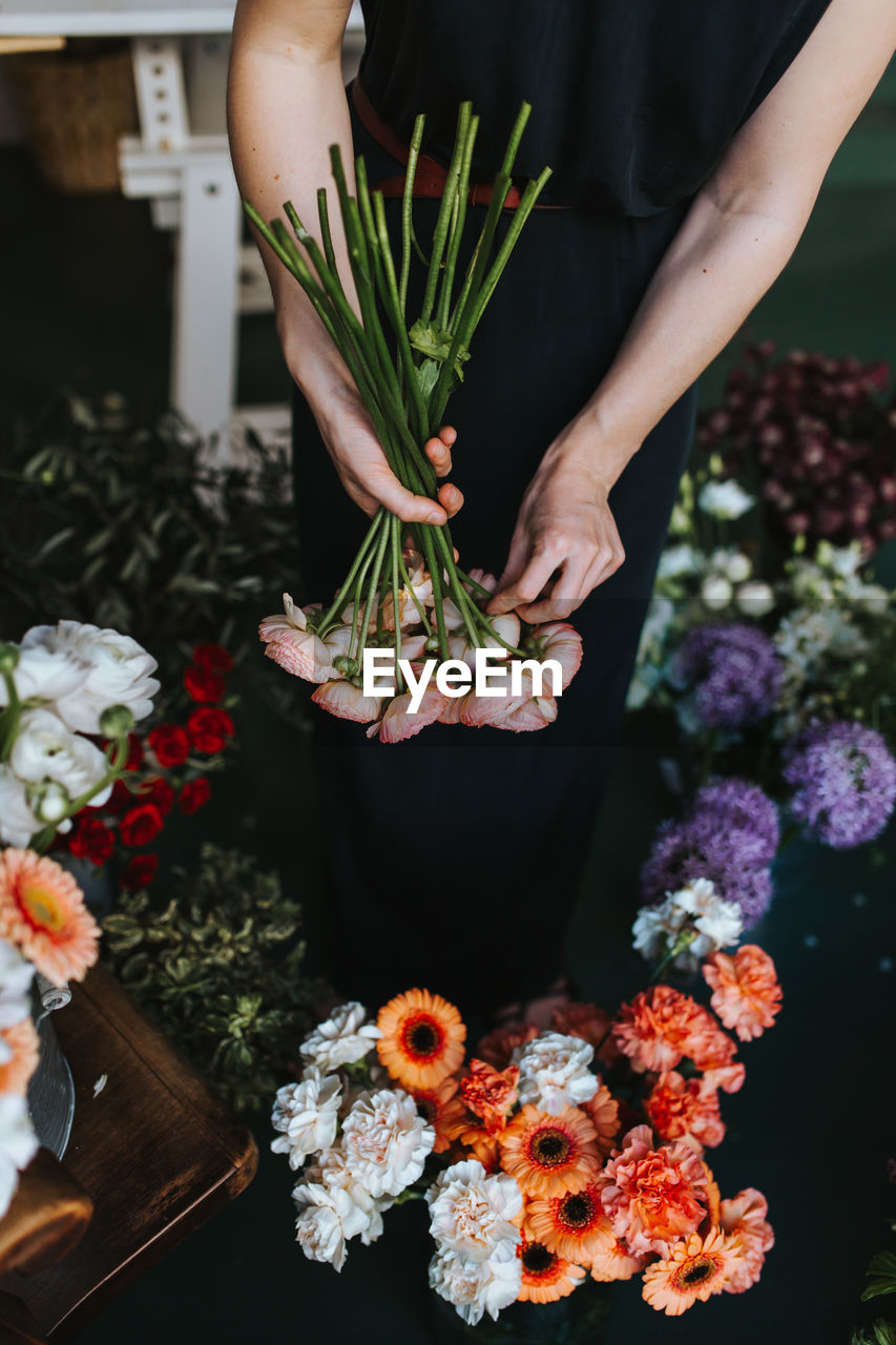 Midsection Of Woman Holding Bouquet In Flower Shop