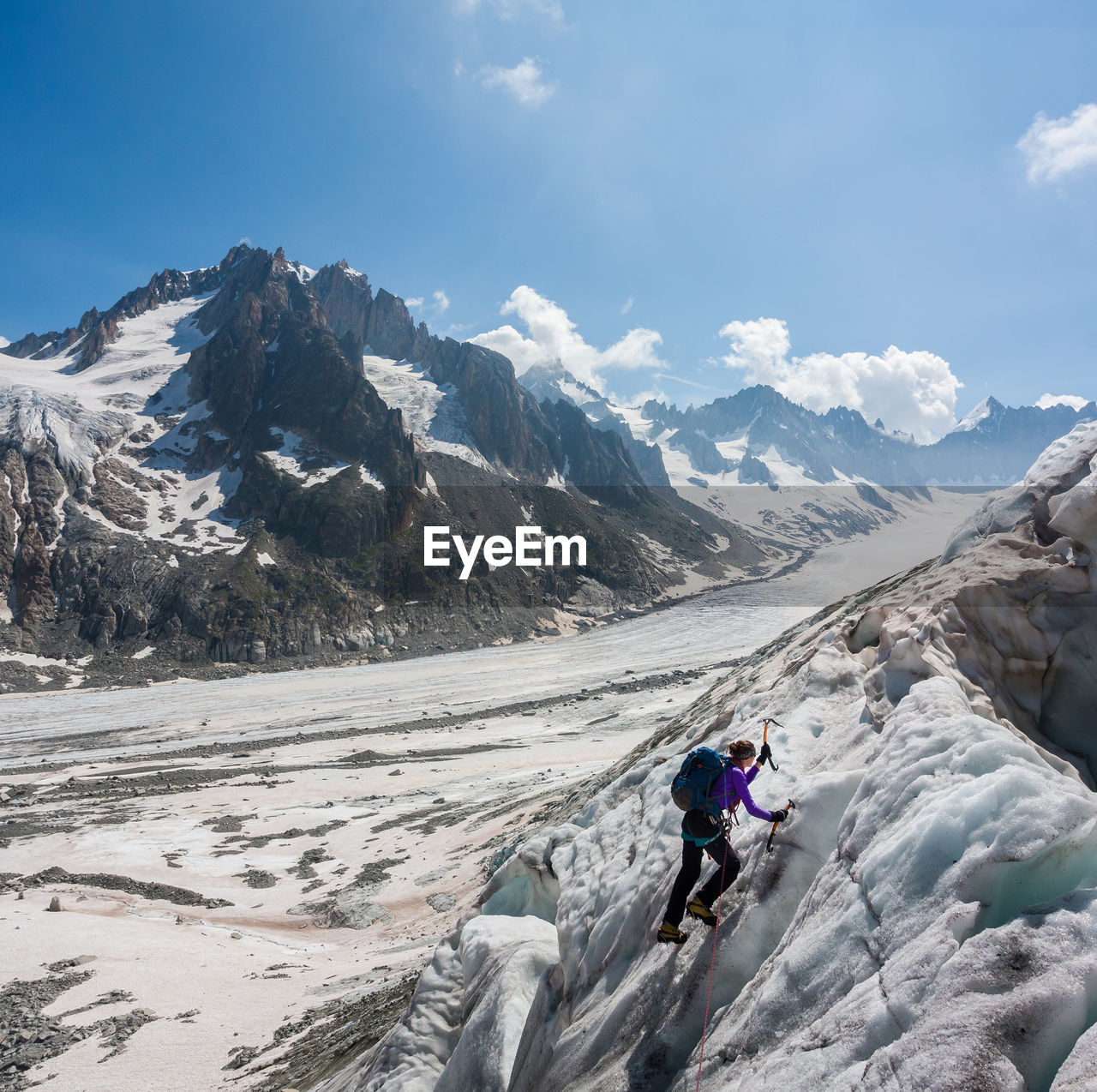 Woman climbing on snowcapped mountain against sky
