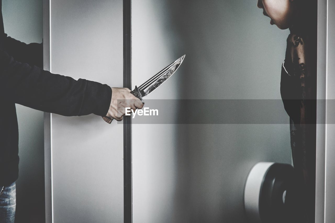 Cropped Image Of Thief Showing Knife To Woman