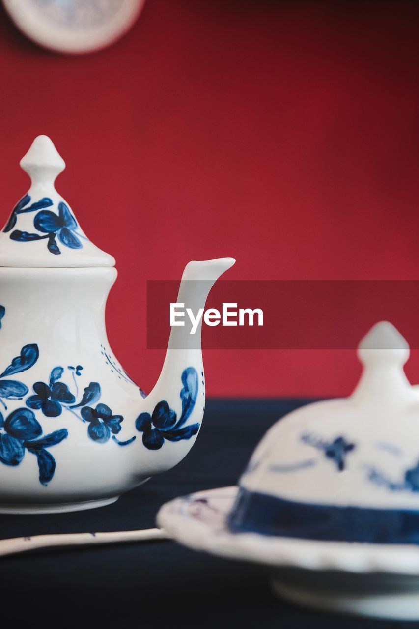 ceramics, still life, teapot, indoors, no people, close-up, porcelain, art and craft, table, kettle, pattern, cup, white color, blue, design, creativity, red, drink, food and drink, mug, crockery, floral pattern, tea cup, antique