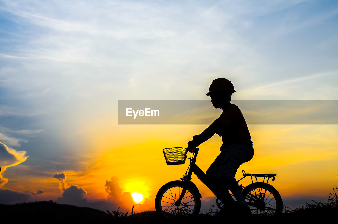 Silhouette Boy Riding Bicycle On Field Against Sky During Sunset