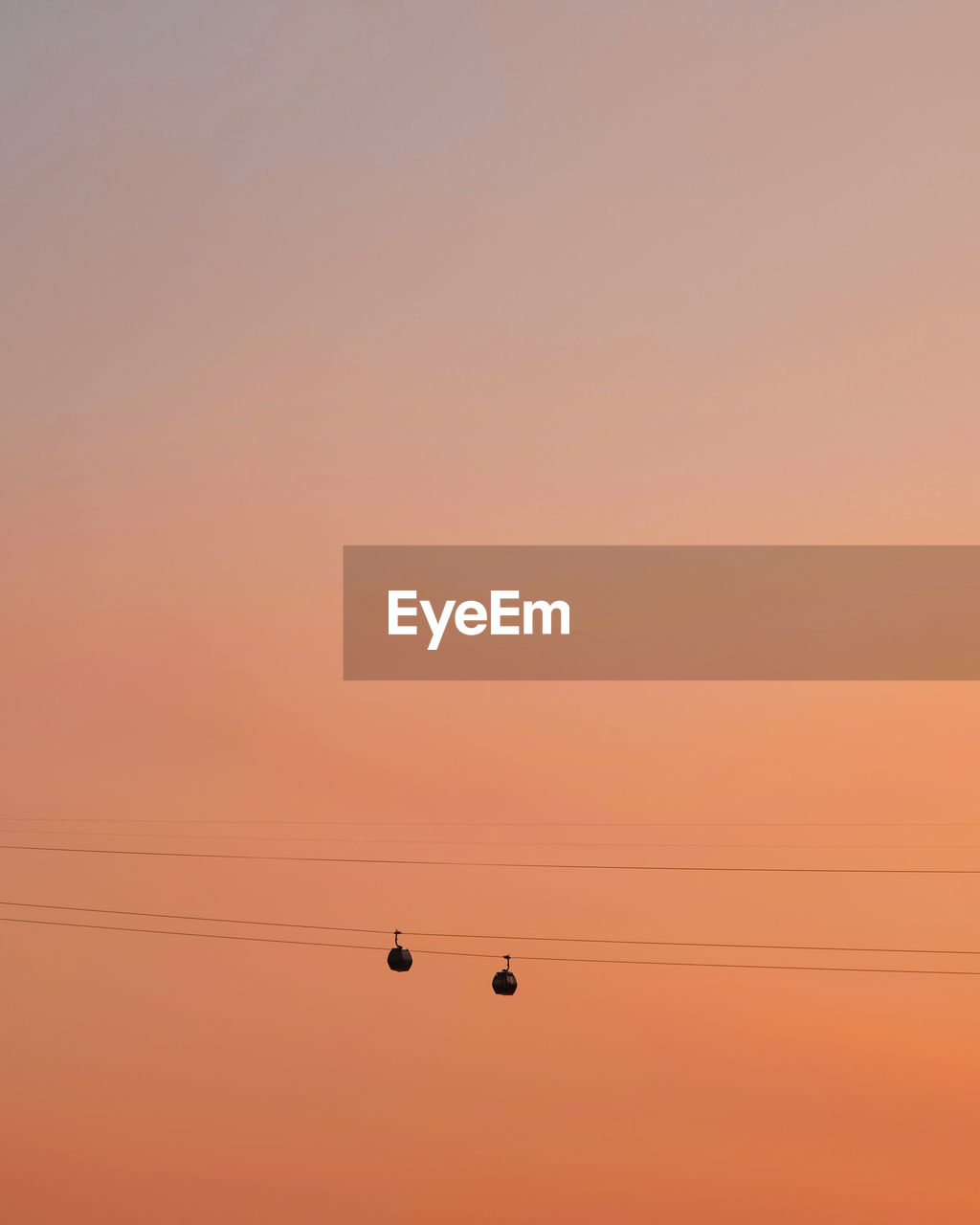 sky, sunset, orange color, cable, beauty in nature, silhouette, no people, electricity, copy space, nature, low angle view, scenics - nature, power line, tranquility, outdoors, connection, tranquil scene, technology, clear sky, idyllic, power supply, romantic sky, electrical equipment