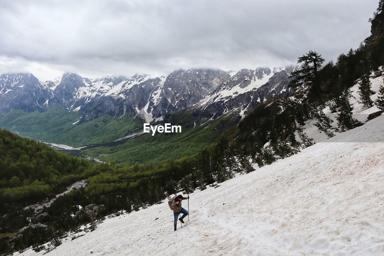 PEOPLE WALKING ON SNOWCAPPED MOUNTAINS AGAINST SKY