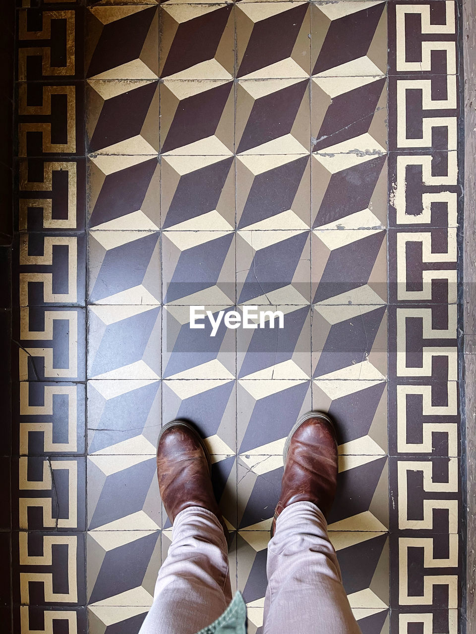LOW SECTION VIEW OF MAN STANDING ON TILED FLOOR
