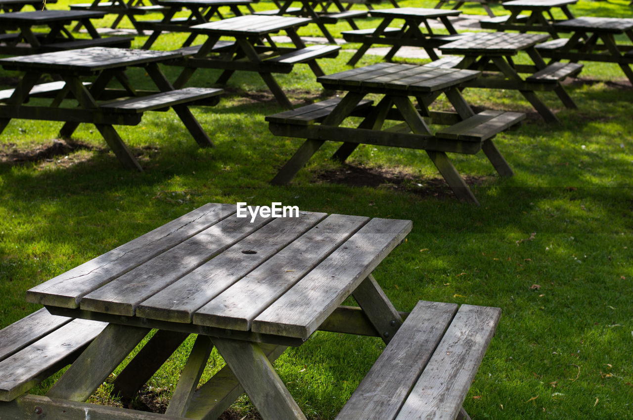 Empty wooden picnic tables arranged on grassy field