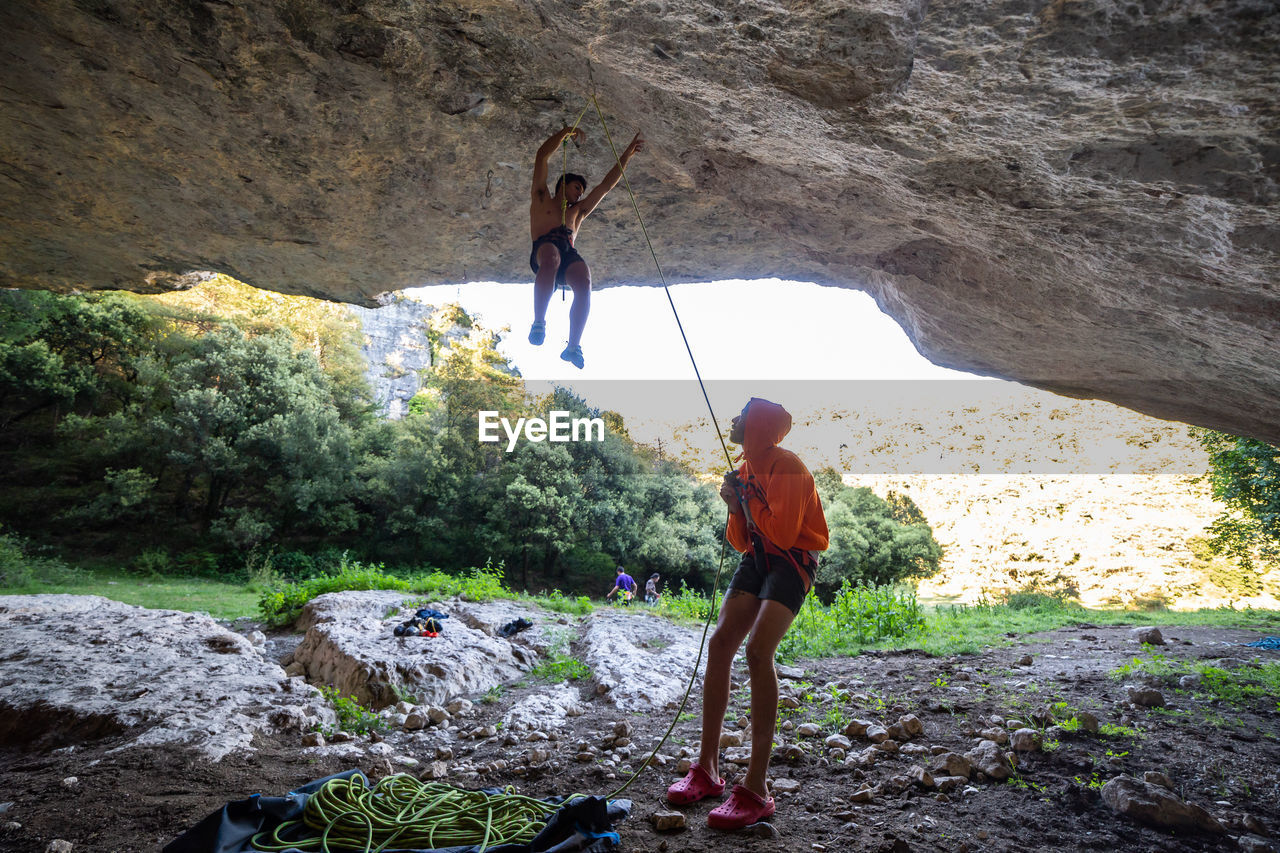 Man with friend balancing on rope in cave