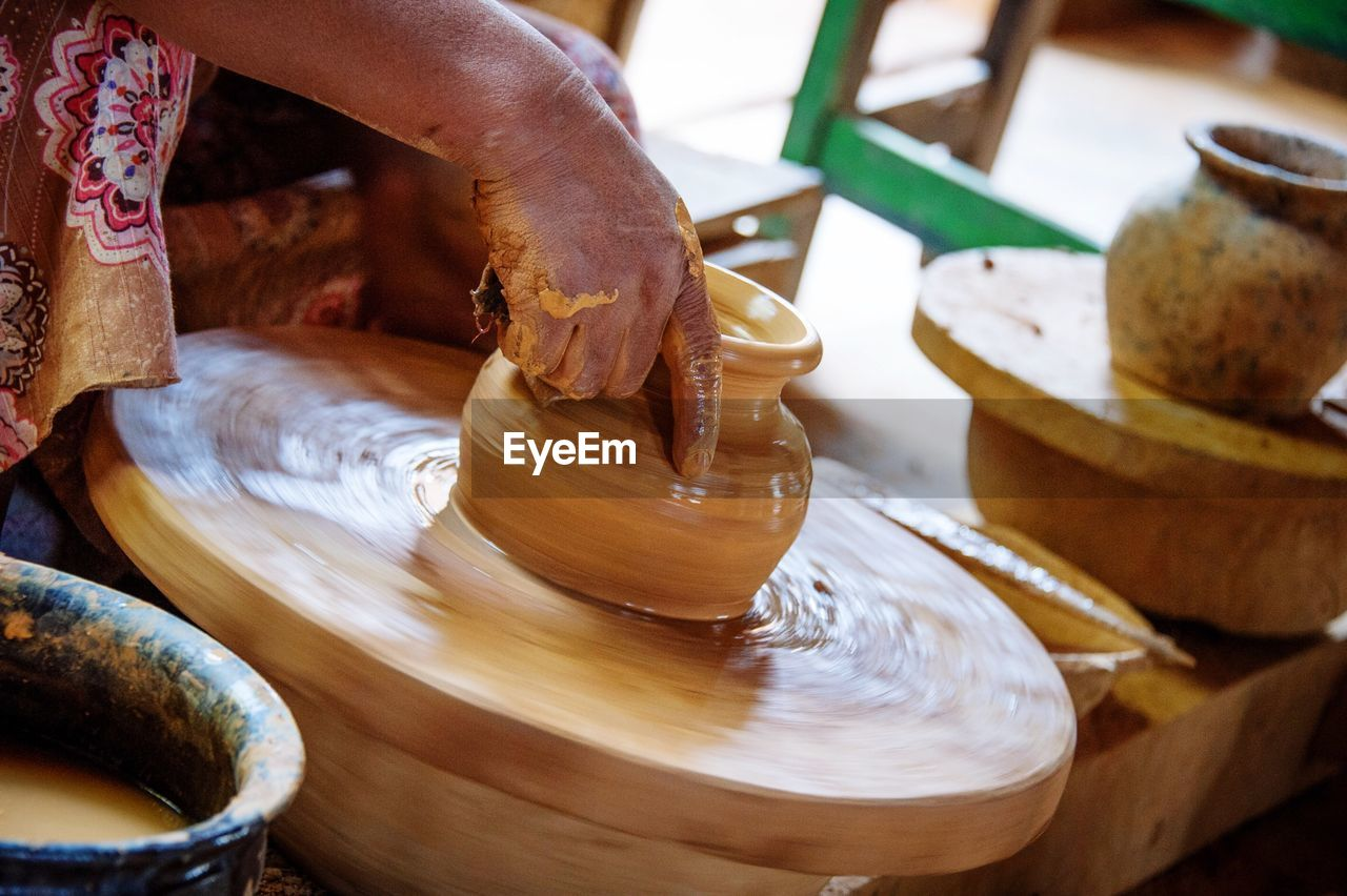 art and craft, clay, motion, indoors, human hand, skill, earthenware, wood - material, focus on foreground, expertise, human body part, workshop, craftsperson, close-up, working, real people, day, one person