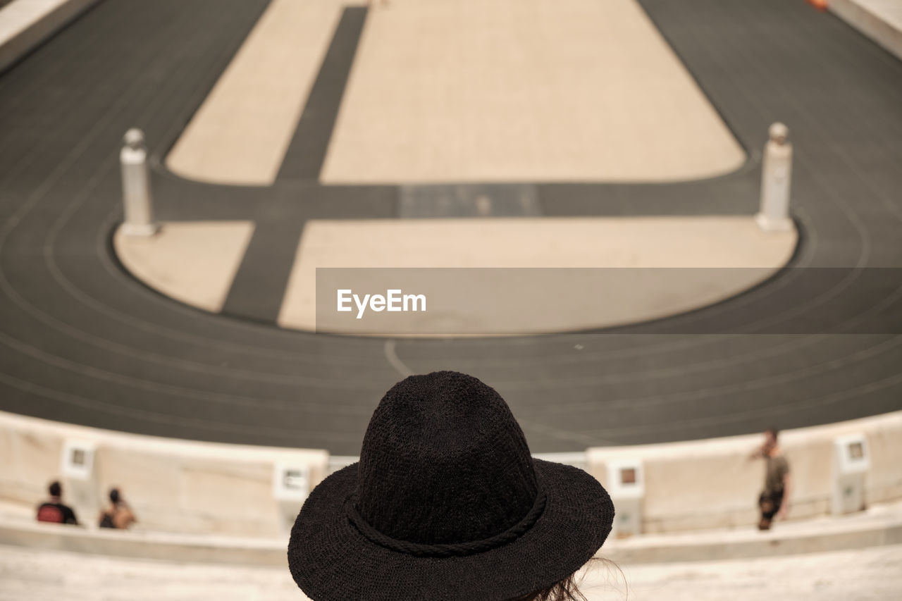 real people, rear view, lifestyles, one person, architecture, focus on foreground, leisure activity, built structure, day, headshot, hat, unrecognizable person, shape, incidental people, men, activity, arts culture and entertainment, high angle view, outdoors