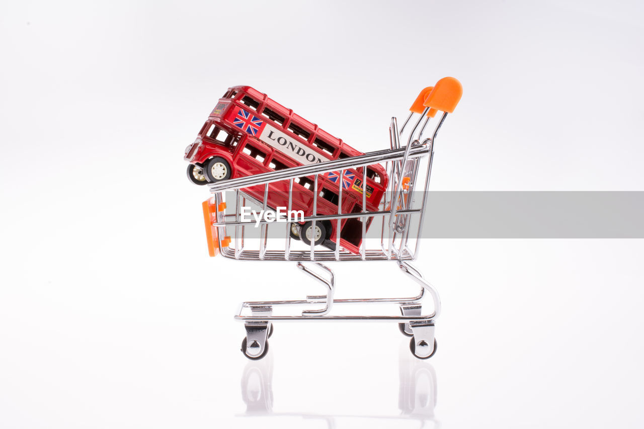 shopping cart, studio shot, shopping, white background, consumerism, indoors, retail, cut out, still life, no people, red, store, copy space, supermarket, metal, close-up, single object, business, container, finance, groceries, shopping basket, economy