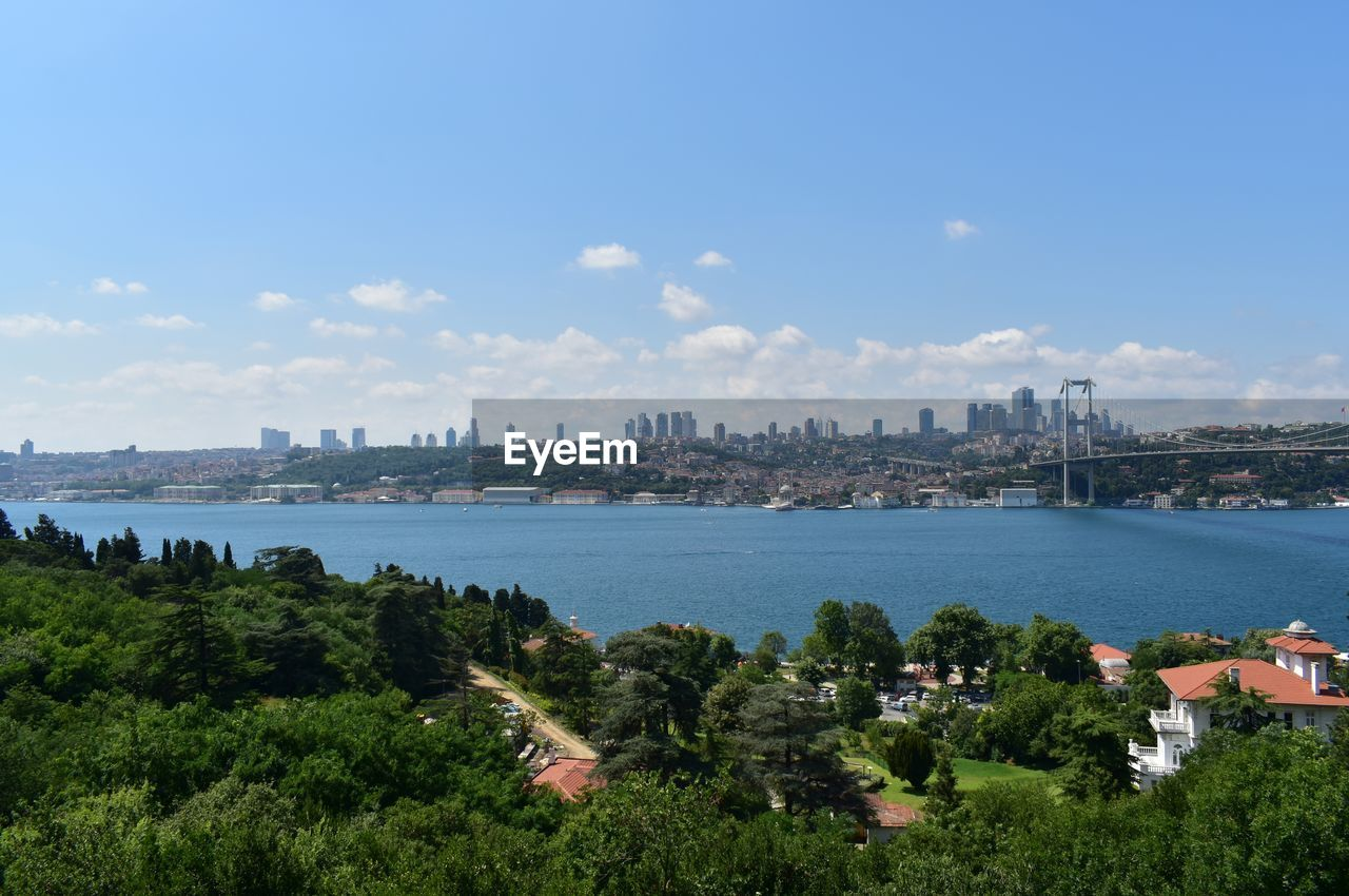 SCENIC VIEW OF CITY BY SEA AGAINST SKY