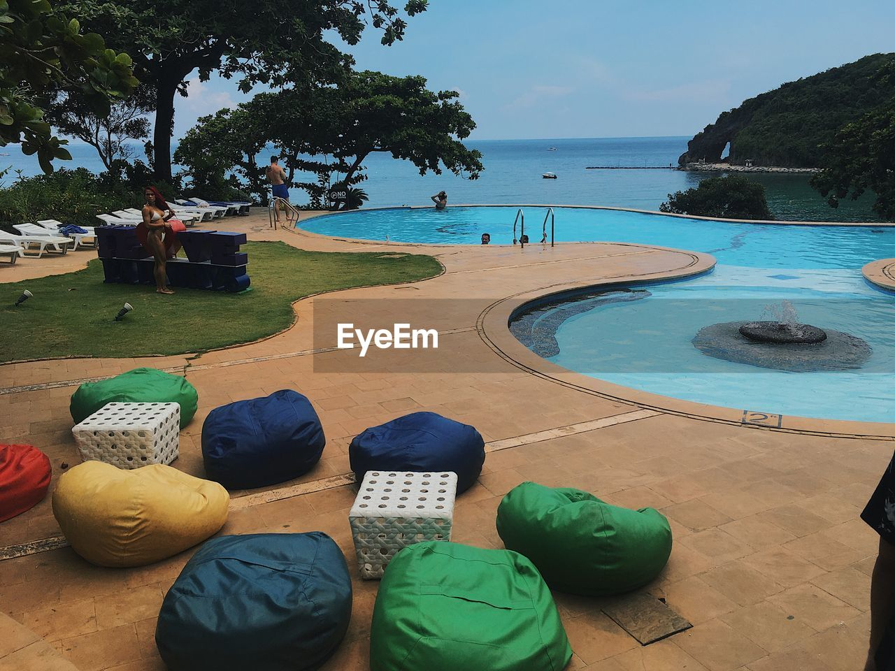 water, pool, tree, sea, swimming pool, plant, nature, day, incidental people, real people, leisure activity, land, beach, blue, relaxation, vacations, trip, group of people, holiday, outdoors