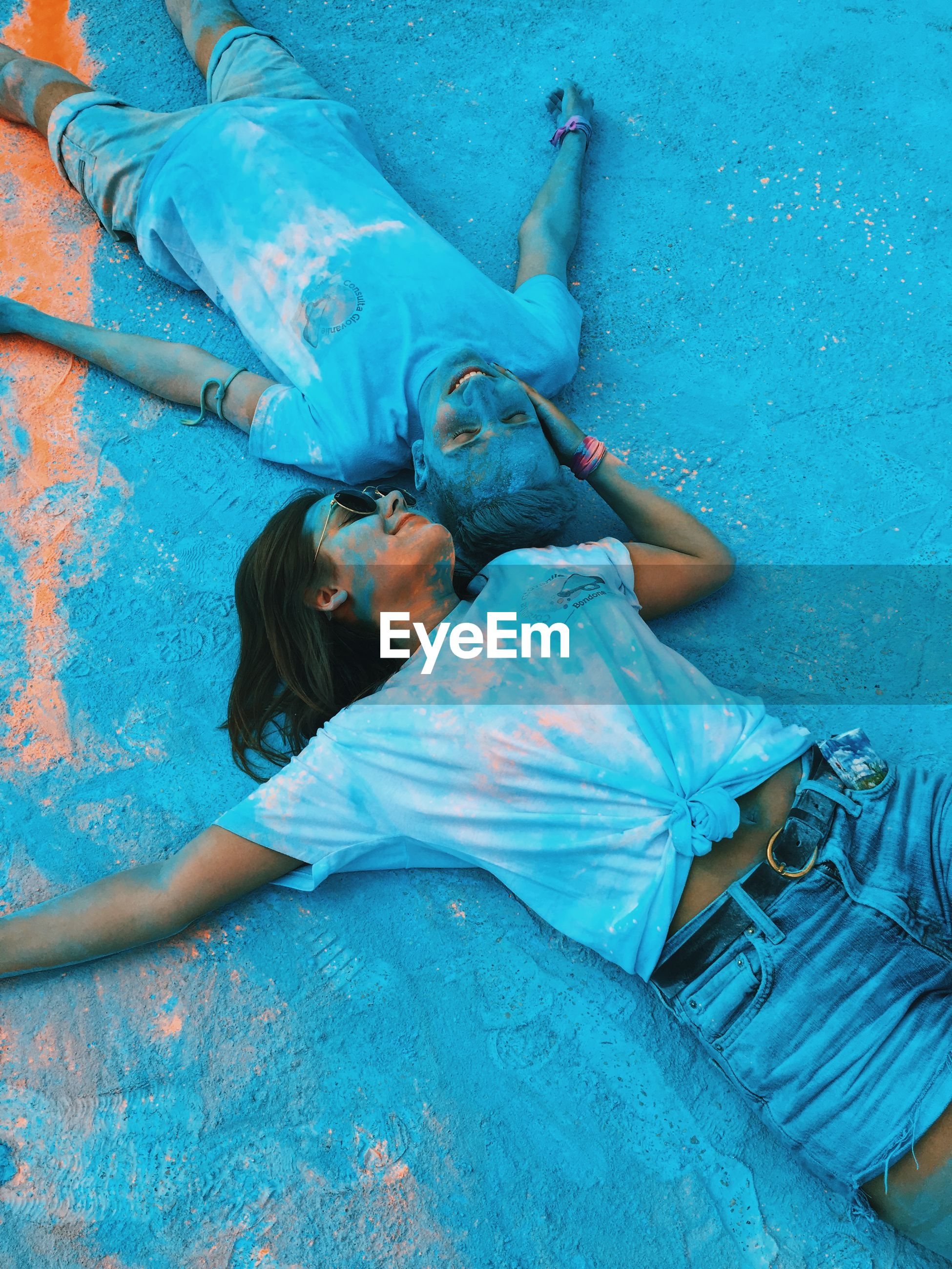 High angle view of young couple lying down on powder paint