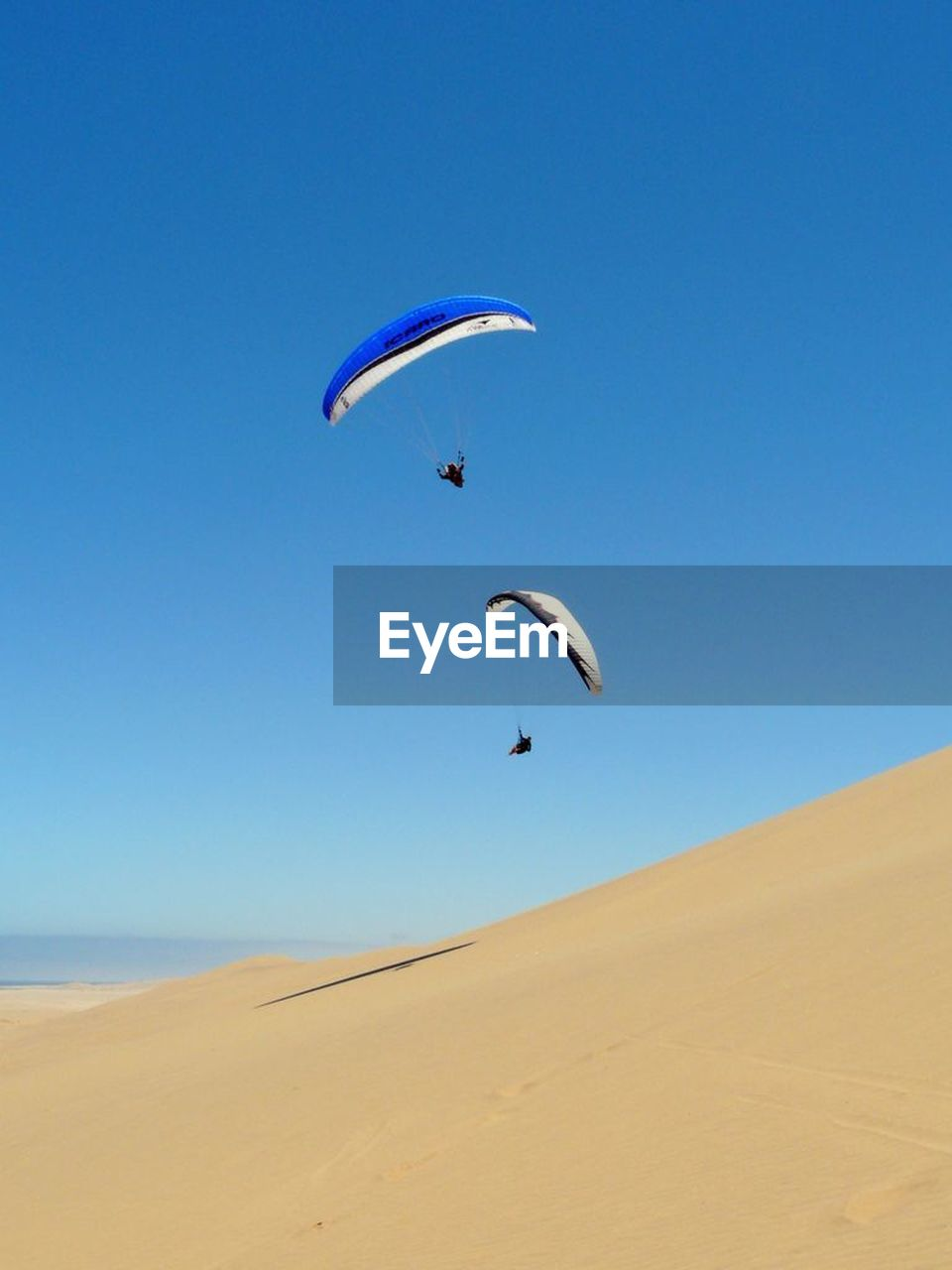 beach, sand, parachute, extreme sports, paragliding, adventure, nature, leisure activity, sky, sport, one person, scenics, day, vacations, full length, outdoors, arid climate, sea, mid-air, clear sky, sand dune, landscape, blue, travel destinations, lifestyles, desert, one man only, beauty in nature, people, adult