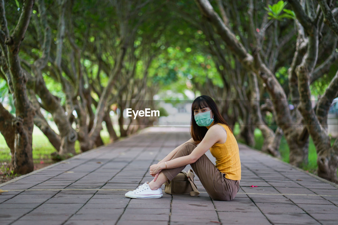 Portrait of young woman wearing mask and sitting by tree